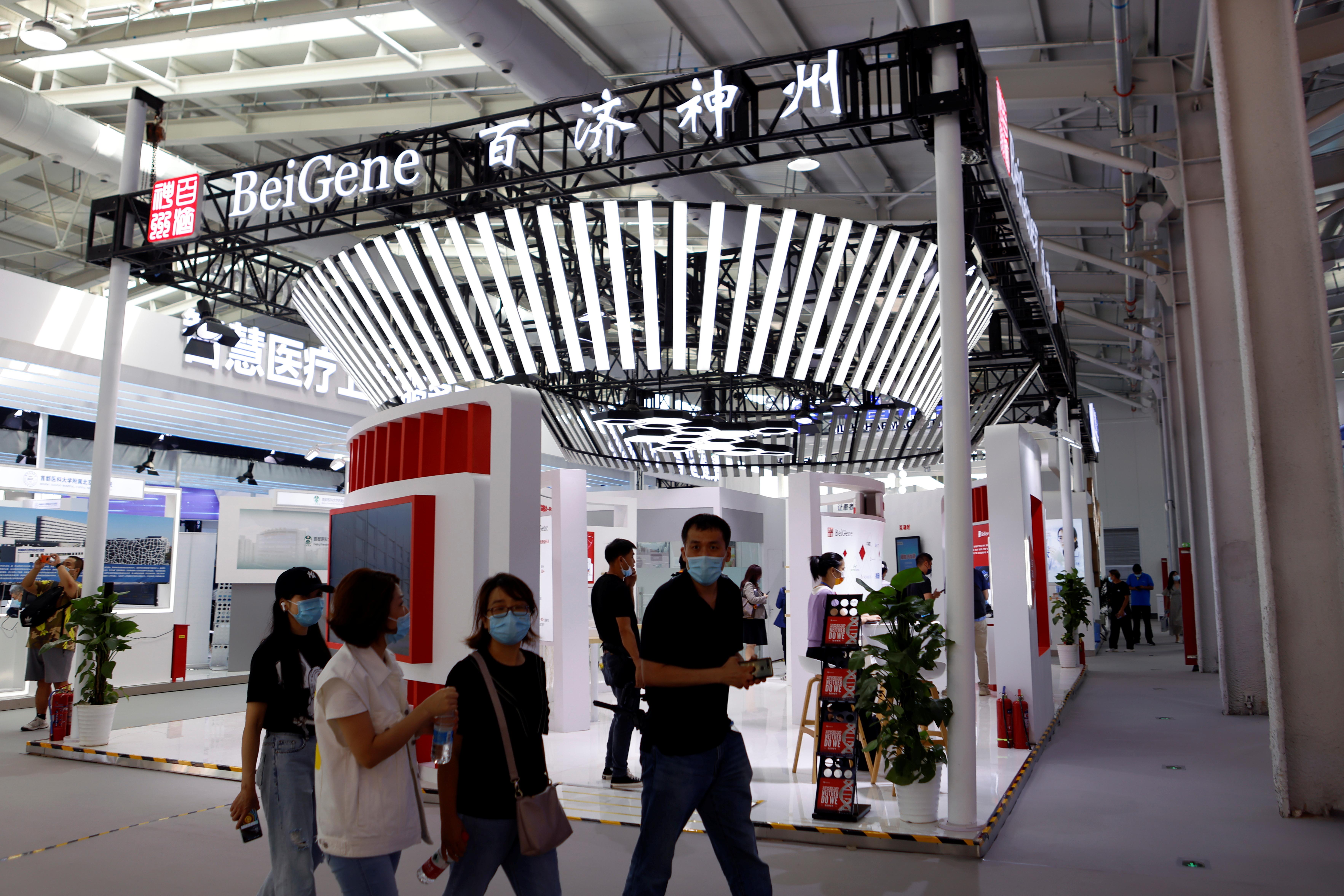 People walk past a booth of biotech company Beigene at the 2021 China International Fair for Trade in Services (CIFTIS) in Beijing, China September 3, 2021. REUTERS/Florence Lo