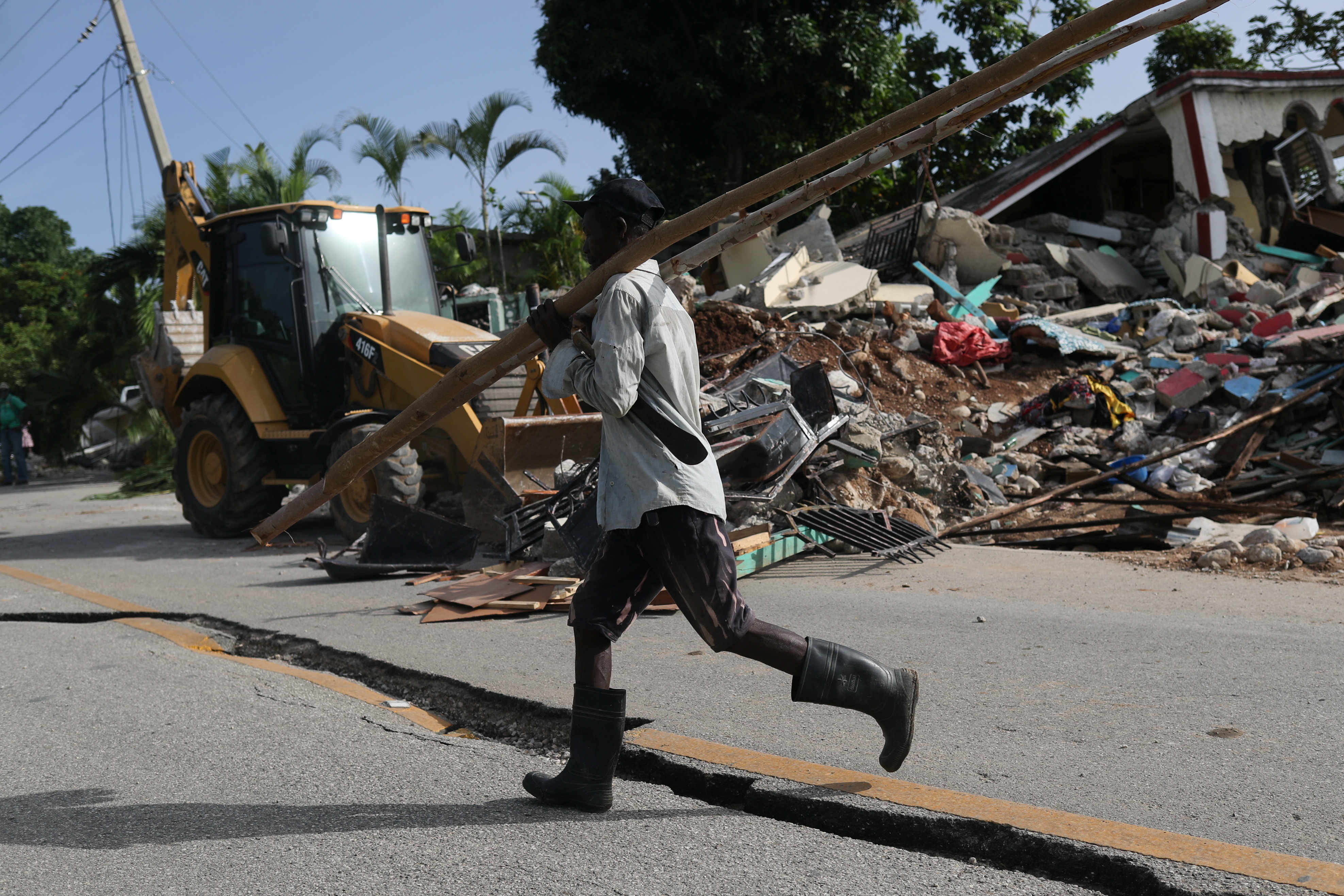 A man walks on a damaged road, after the earthquake that took place on August 14th, in Marceline, near Les Cayes, Haiti August 20, 2021. REUTERS/Henry Romero