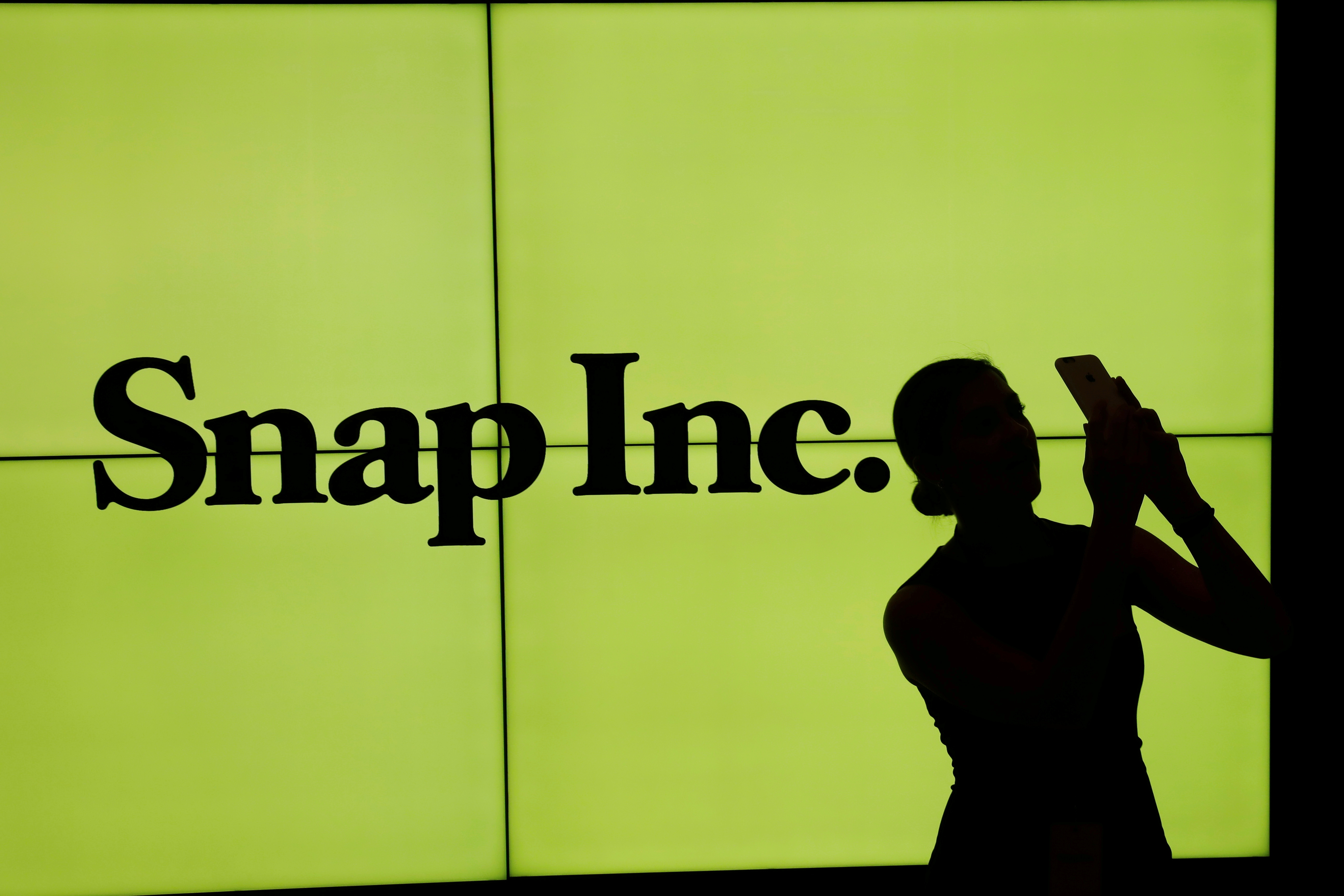 A woman stands in front of the logo of Snap Inc on the floor of the New York Stock Exchange (NYSE) in New York City, NY, U.S. March 2, 2017. REUTERS/Lucas Jackson