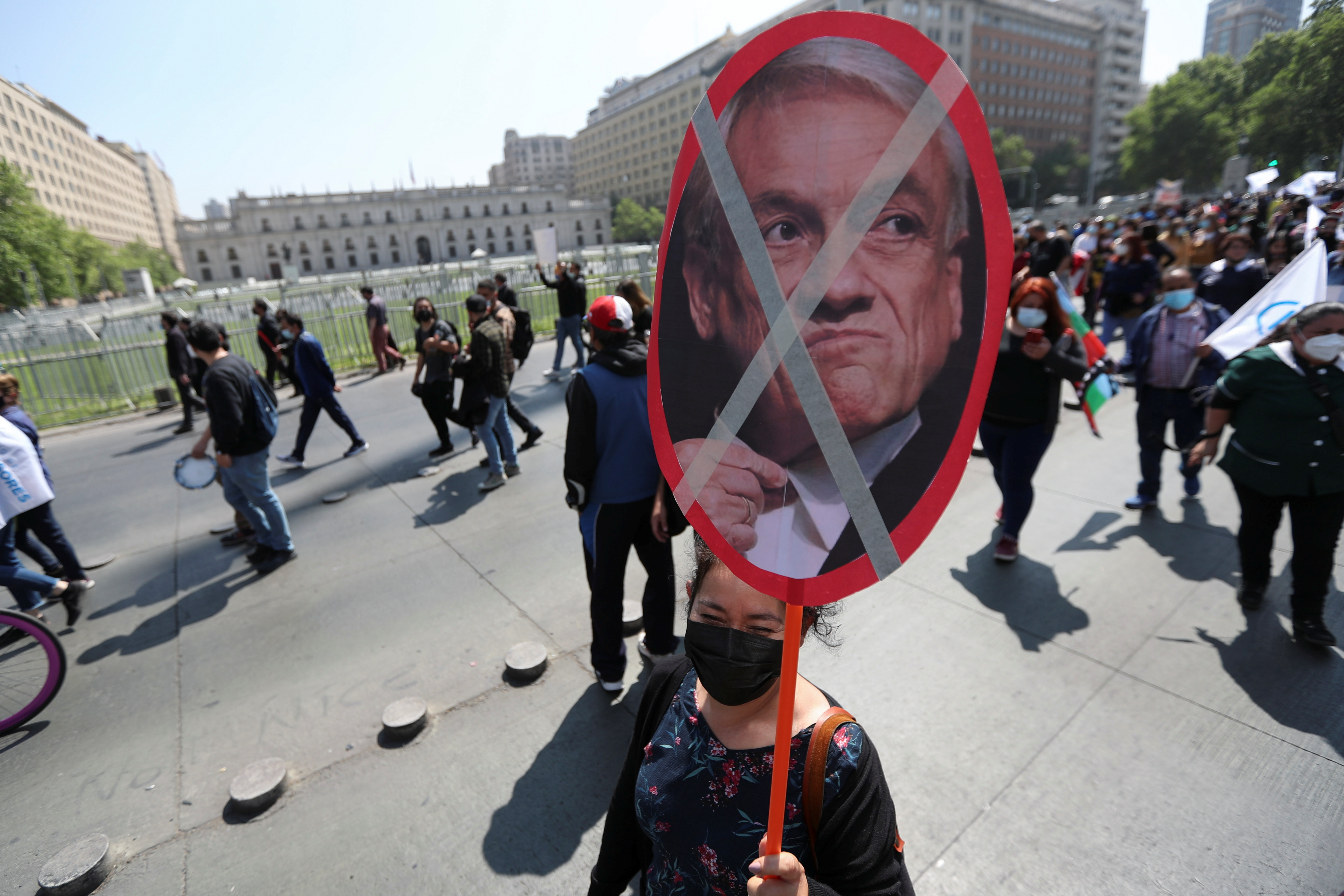 A demonstrator holds up a banner with the image of Chile's President Sebastian Pinera in front of the government house during a rally calling for the cancellation of a presidential veto of a bill that would improve the working conditions of Chilean teachers, and to request Pinera's resignation, in Santiago, Chile, October 13, 2021. REUTERS/Ivan Alvarado