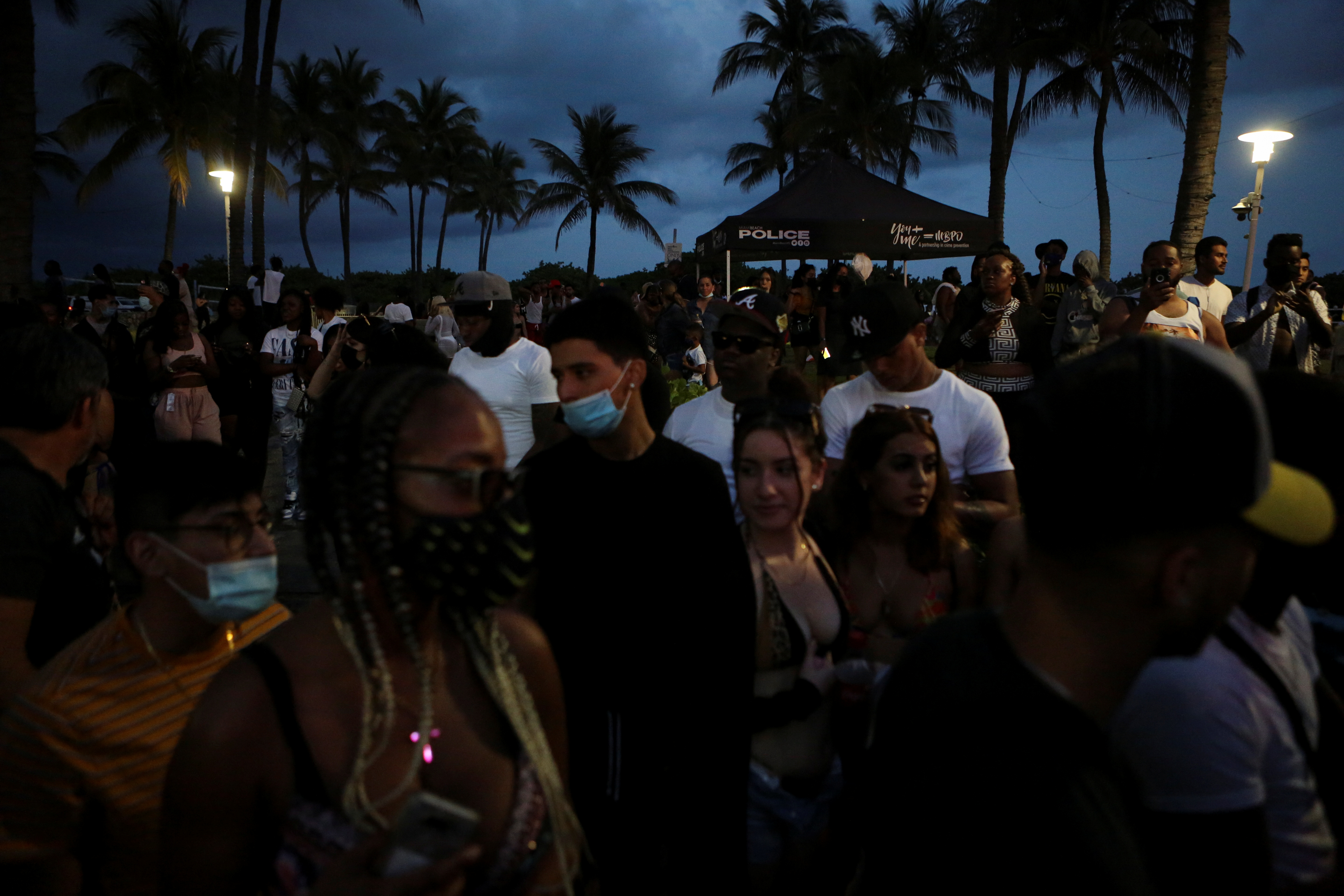 People walk along Ocean Drive during spring break festivities ahead of an 8pm curfew imposed by local authorities, amid the coronavirus disease (COVID-19) outbreak in Miami Beach, Florida, U.S., March 20, 2021. REUTERS/Marco Bello