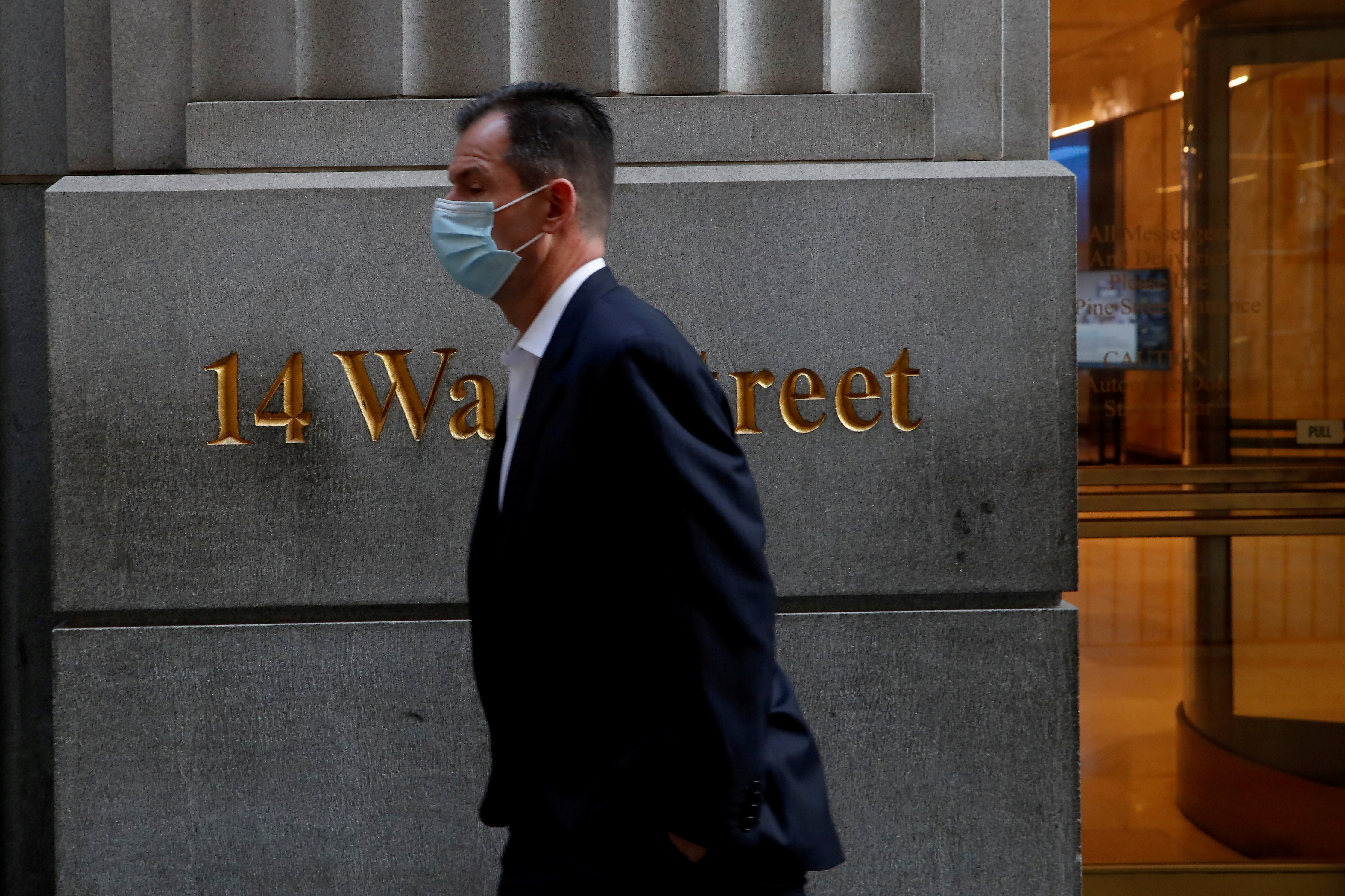 A man wearing a protective face mask walks by 14 Wall Street in the financial district of New York, U.S., November 19, 2020. REUTERS/Shannon Stapleton
