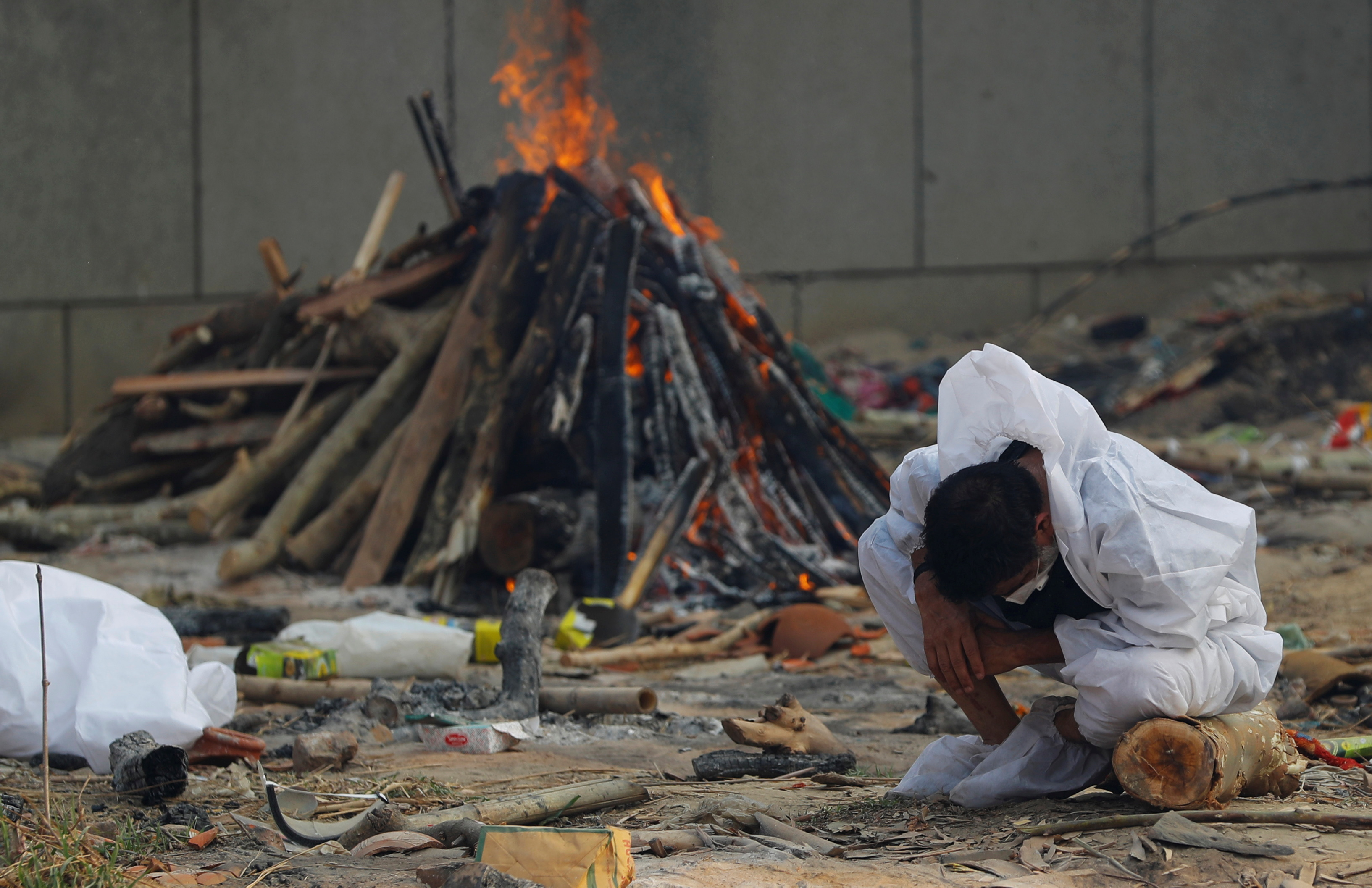 A man mourns as he sits next to the burning pyre of a relative, who died from the coronavirus disease (COVID-19), during his cremation, at a crematorium in New Delhi, India May 5, 2021. REUTERS/Adnan Abidi
