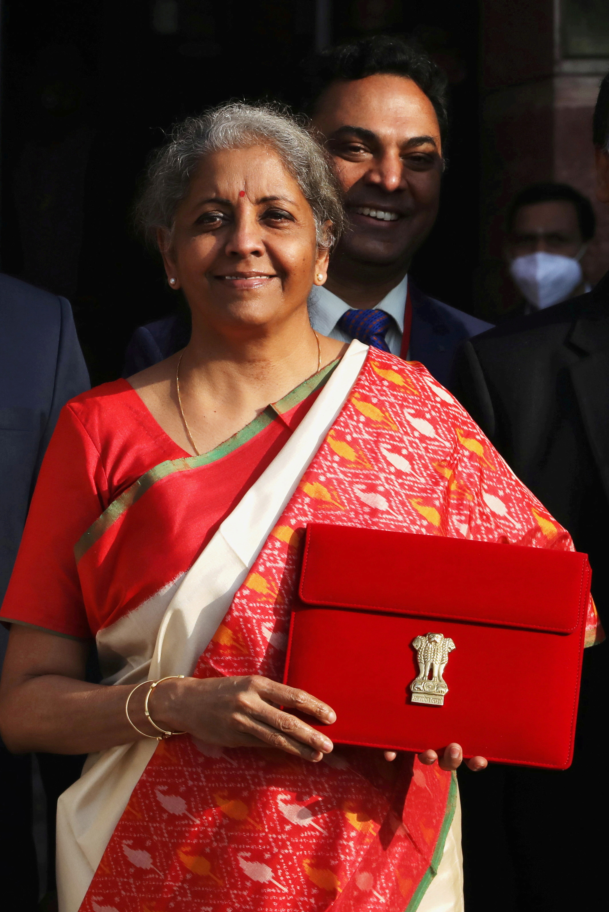 India's Finance Minister Nirmala Sitharaman holds up a folder with the Government of India logo, while India's Chief Economic Advisor Krishnamurthy Subramanian looks on (at rear), as she leaves her office to present the federal budget in the parliament in New Delhi, India, February 1, 2021. REUTERS/Anushree Fadnavis/File Photo