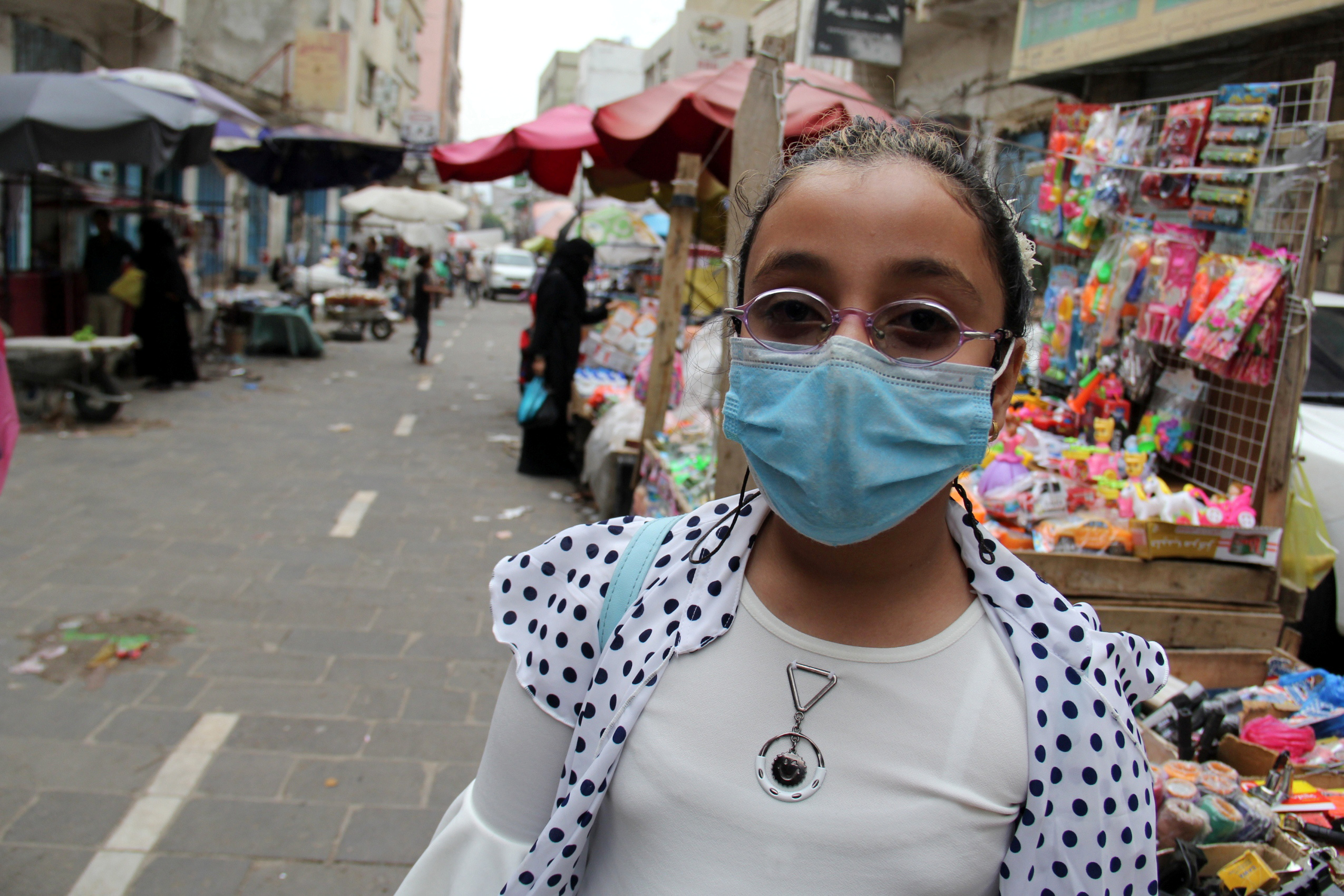 A girl wearing a protective face mask is pictured at a market following the outbreak of the coronavirus disease (COVID-19), in Taiz, Yemen July 5, 2020. Picture taken July 5, 2020. REUTERS/Anees Mahyoub