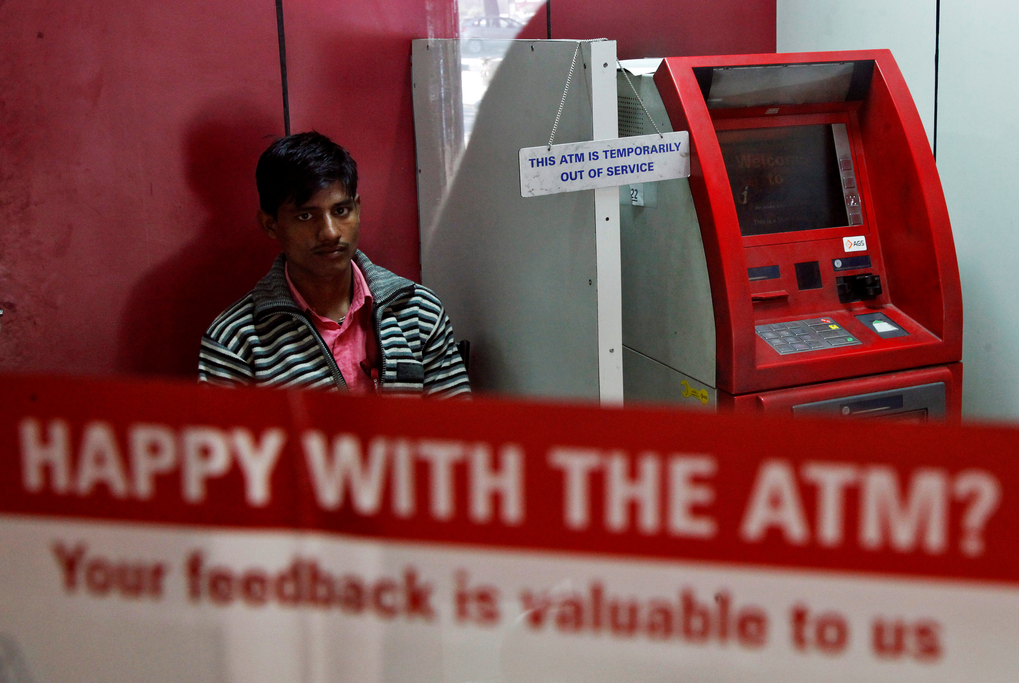 A security guard sits inside an ATM counter as a notice hangs on an ATM machine in Chandigarh, India, November 25, 2016. REUTERS/Ajay Verma