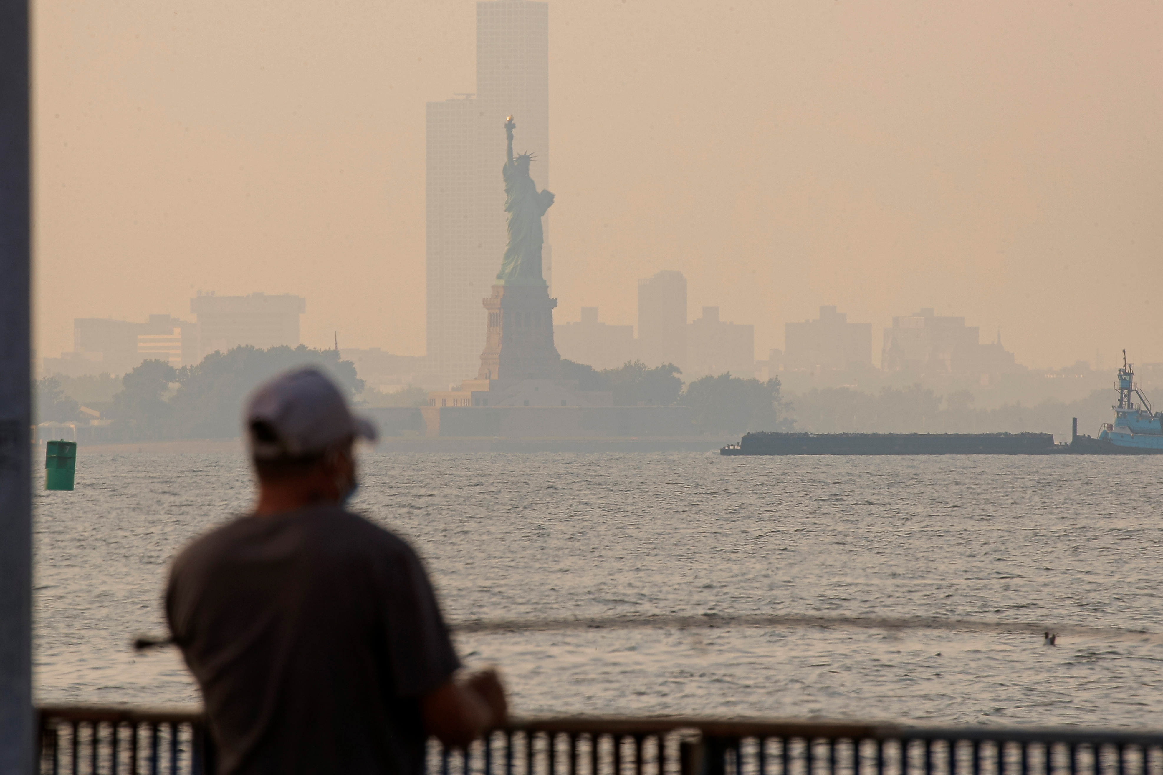 The Statue of Liberty is seen through a cover of wildfire smoke in New York Harbor as seen from Brooklyn, New York, U.S., July 21, 2021.  REUTERS/Brendan McDermid