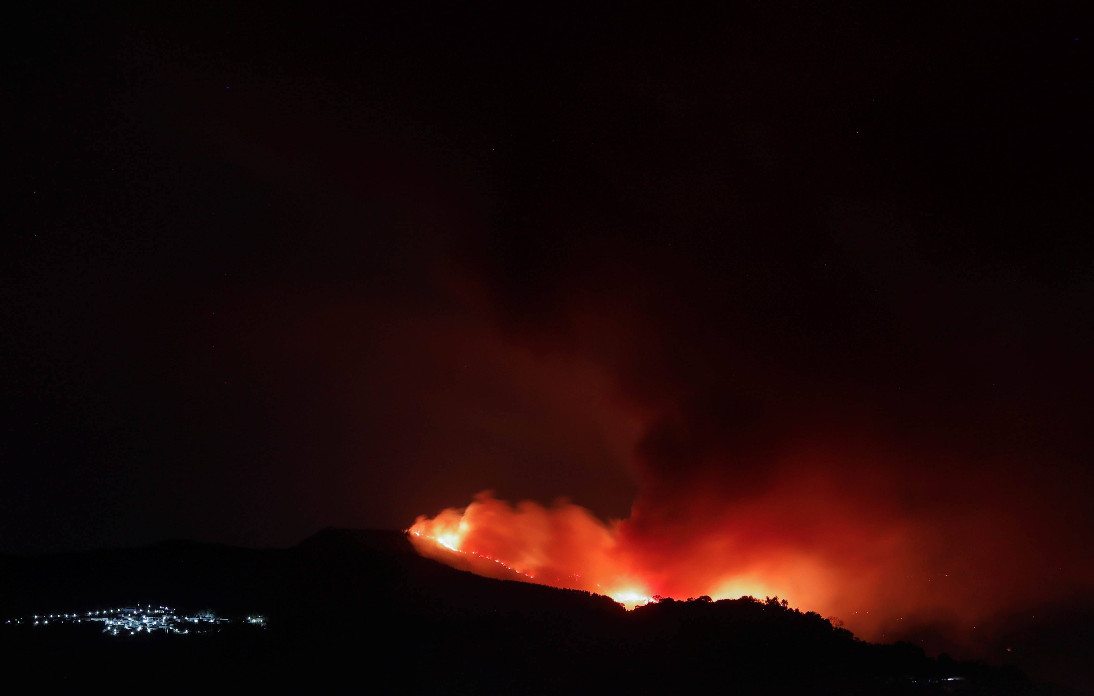 A wildfire is seen from a balcony near the town of Pujerra, which was evacuated, in Cartajima, near Estepona, Spain, September 12, 2021. REUTERS/Jon Nazca