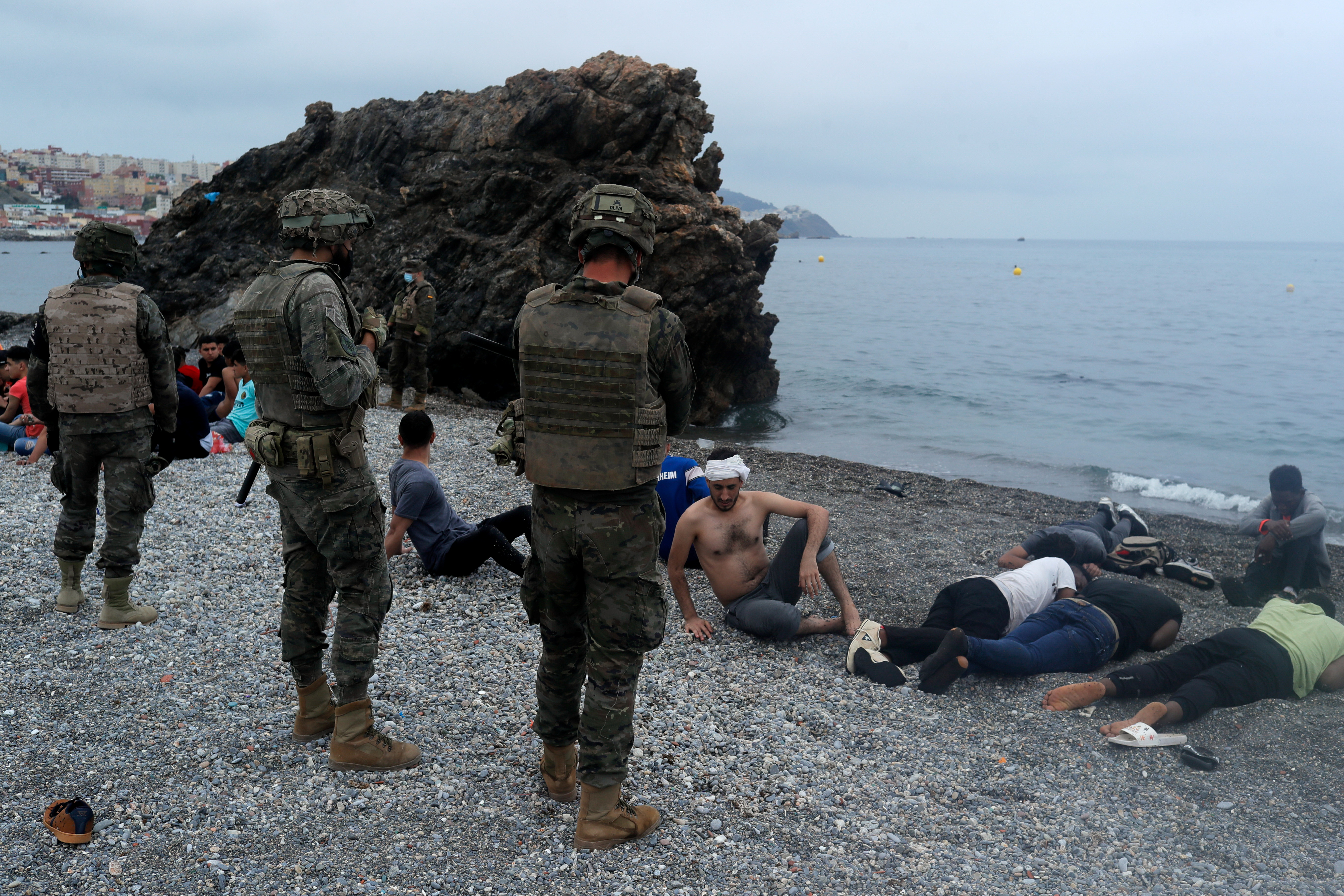 Spanish legionnaires stand around Moroccan citizens as they lie down on El Tarajal beach, next to the fence between the Spanish-Moroccan border, after thousands of Moroccans swam across this border on Monday, in Ceuta, Spain, May 18, 2021. REUTERS/Jon Nazca