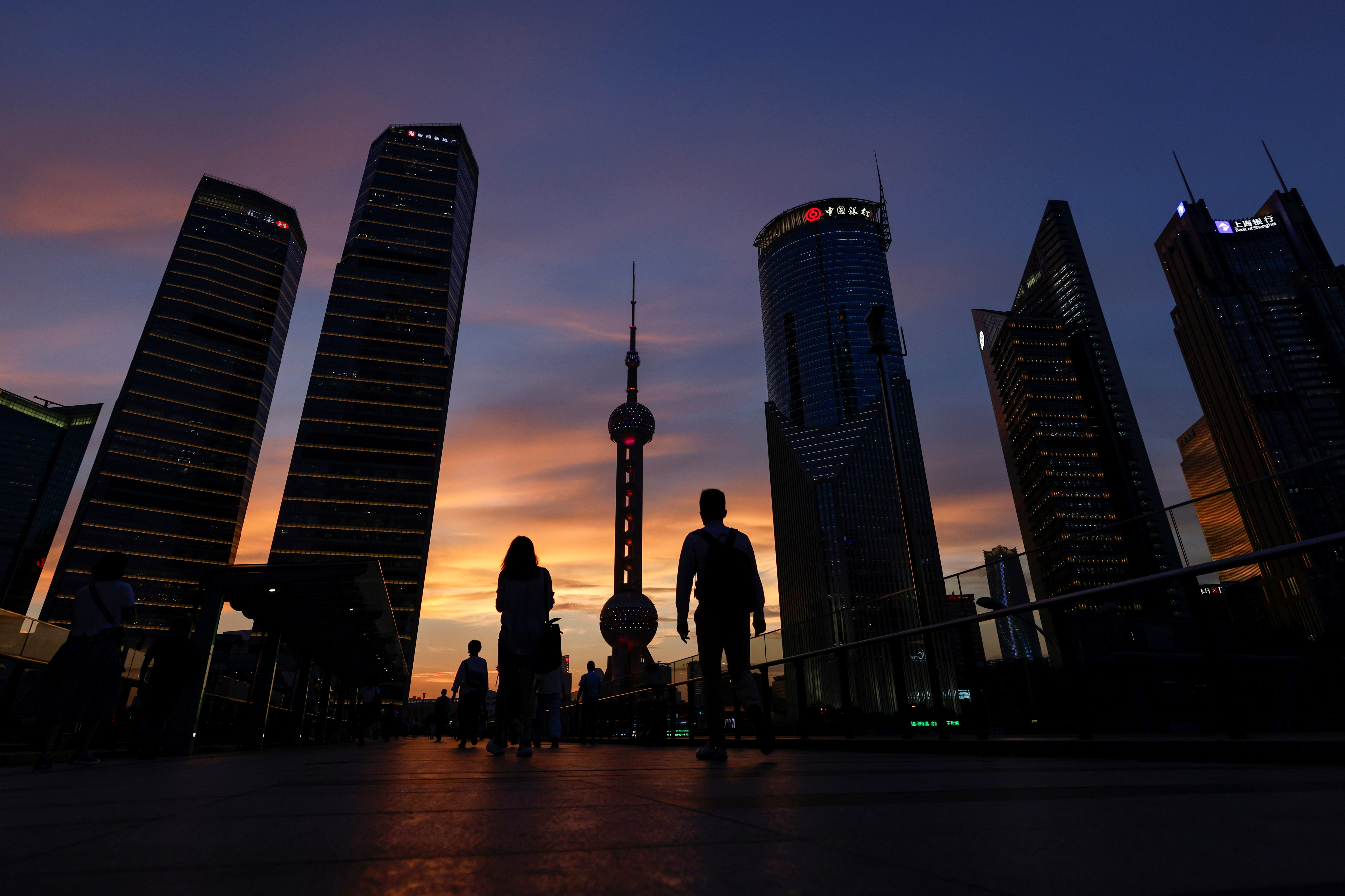 People walk in Lujiazui financial district during sunset in Pudong, Shanghai, China July 13, 2021.   REUTERS/Aly Song