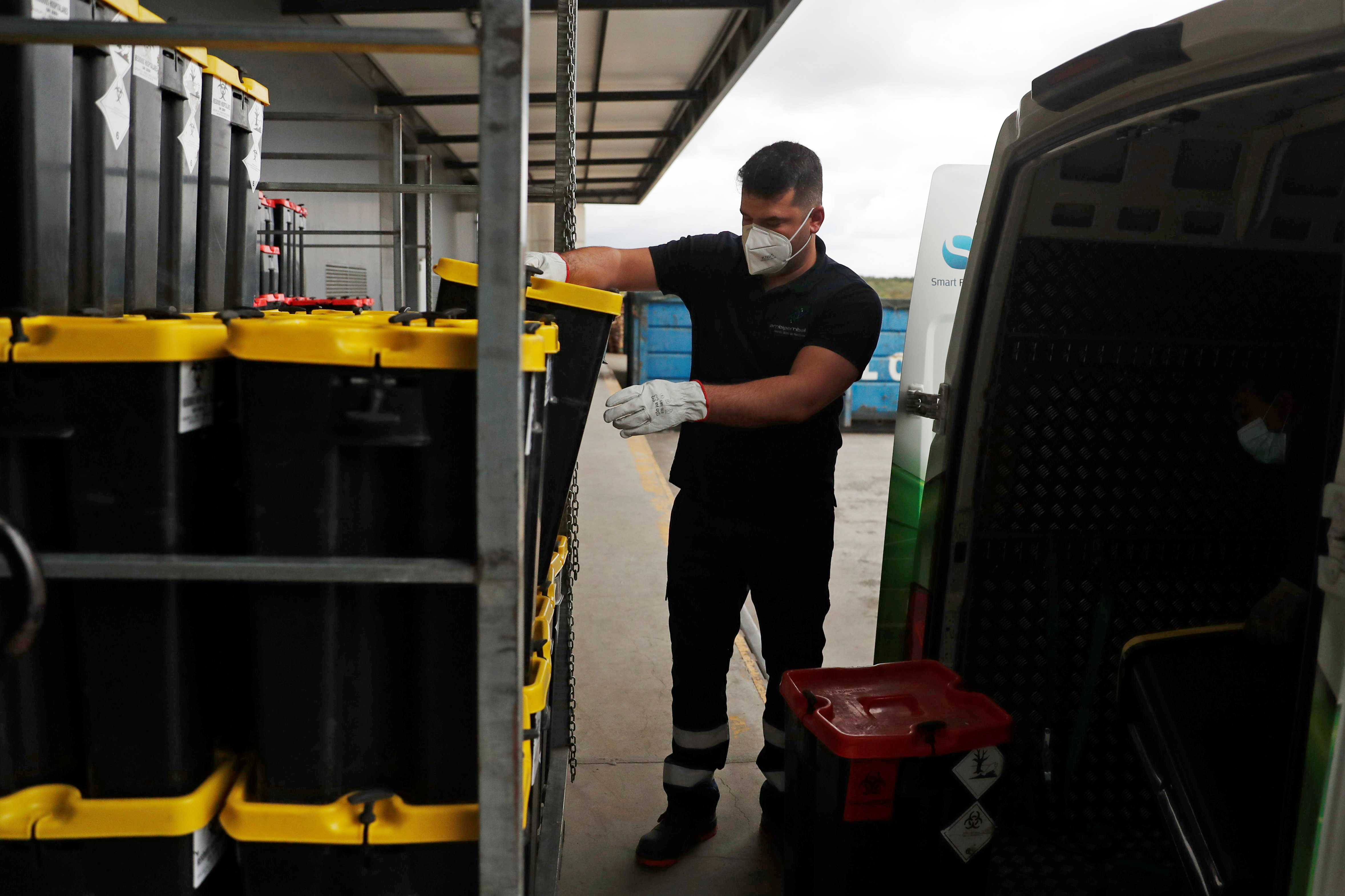 A worker removes containers with used supplies from COVID-19 vaccines and protective equipment from a truck to a pile in a waste treatment facility, amid the coronavirus disease (COVID-19) pandemic, in Chamusca, Santarem, Portugal, April 21, 2021.  REUTERS/Pedro Nunes