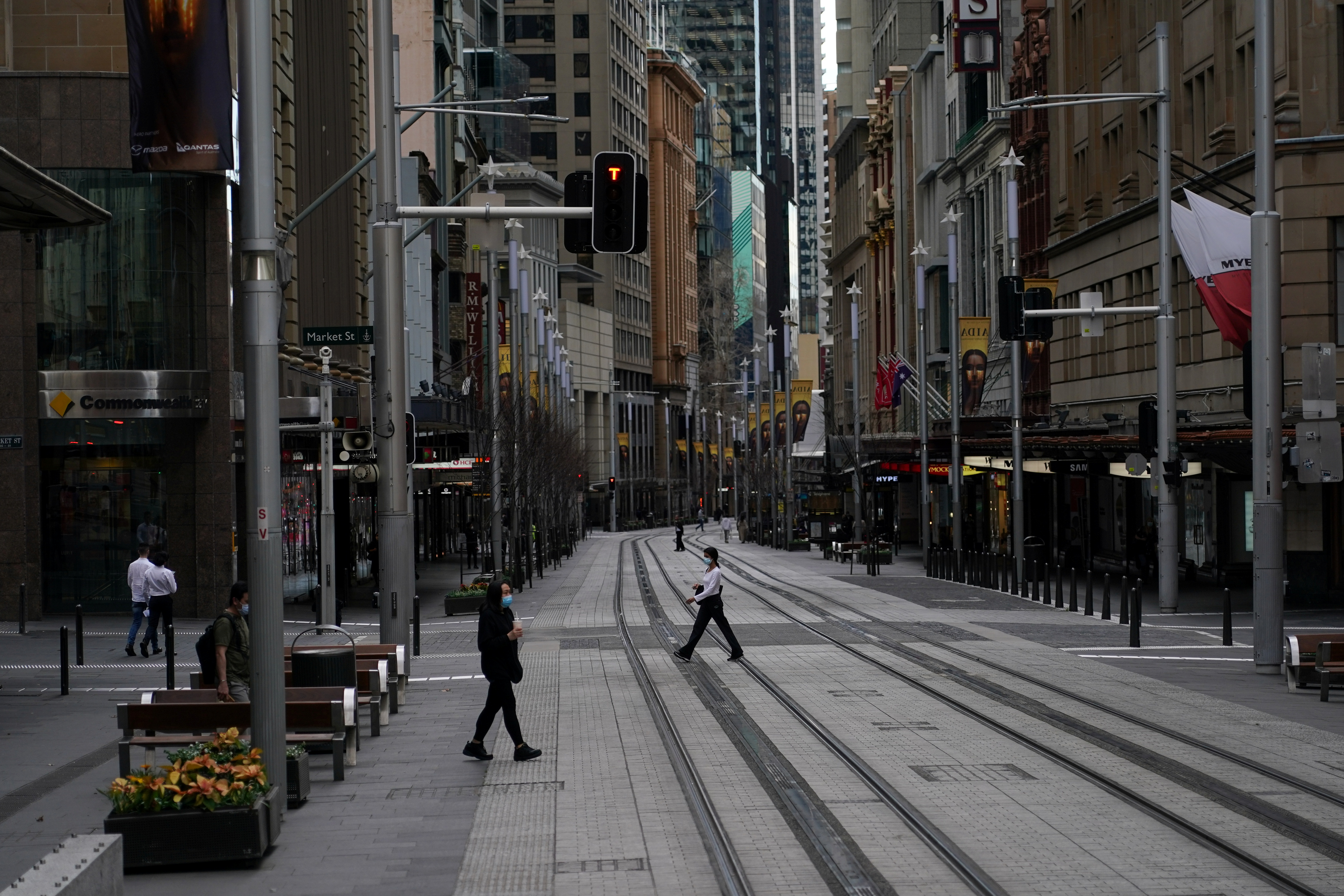 People in protective face masks walk through the quiet city centre during a lockdown to curb the spread of a coronavirus disease (COVID-19) outbreak in Sydney, Australia, July 28, 2021.  REUTERS/Loren Elliott