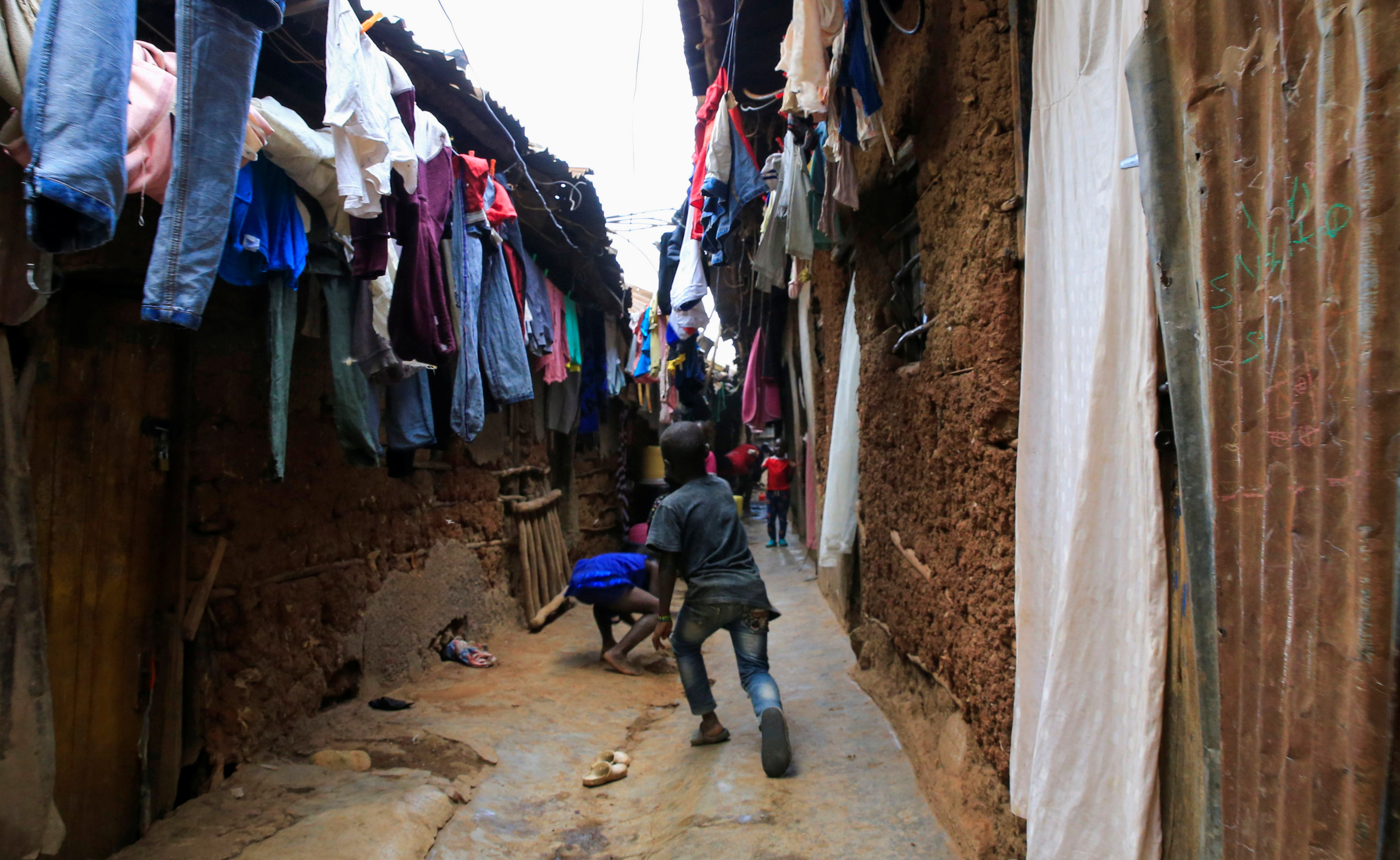 Children play in a courtyard under a hung out laundry amid the coronavirus disease (COVID-19) outbreak, within Kibera slums in Nairobi, Kenya October 6, 2021. REUTERS/Thomas Mukoya