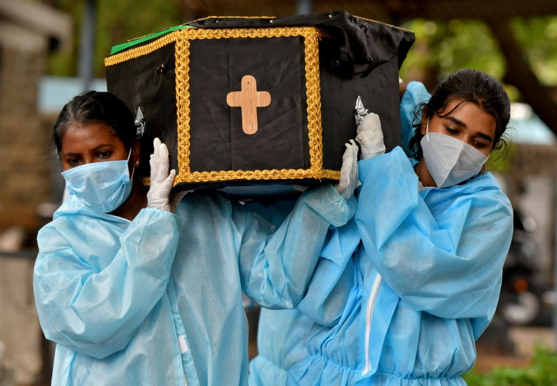 Volunteers, Akshaya (R), 22, a law student, and Esther Mary, 41, a lecturer, carry the body of a person who died from the coronavirus disease (COVID-19) for burial at a cemetery in Bengaluru, India, May 18, 2021. Picture taken May 18, 2021. REUTERS/Samuel Rajkumar