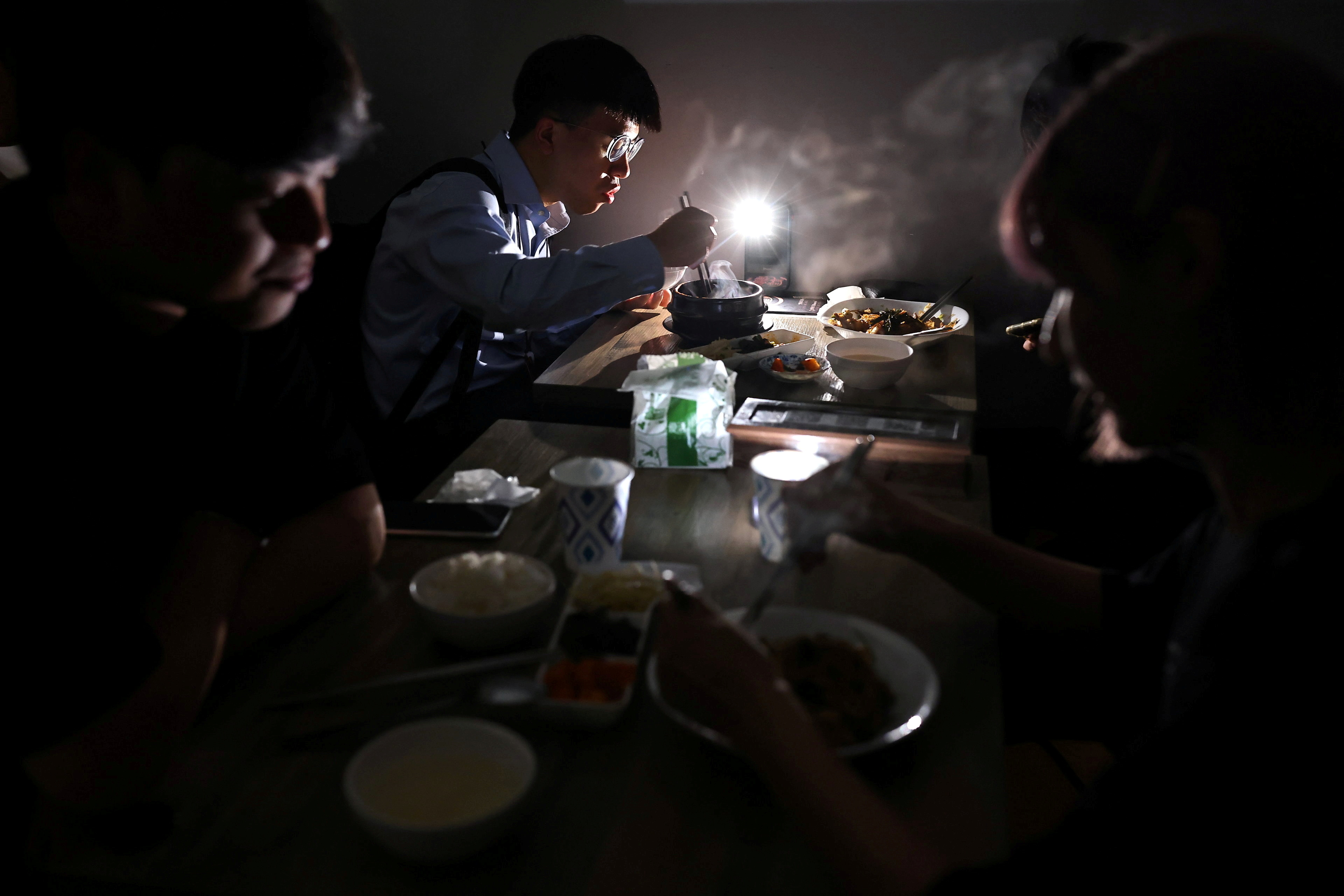 People eat using the light from their phone while experiencing a blackout due to an outage at a power plant, in Taipei, Taiwan, May 13, 2021. REUTER/Ann Wang