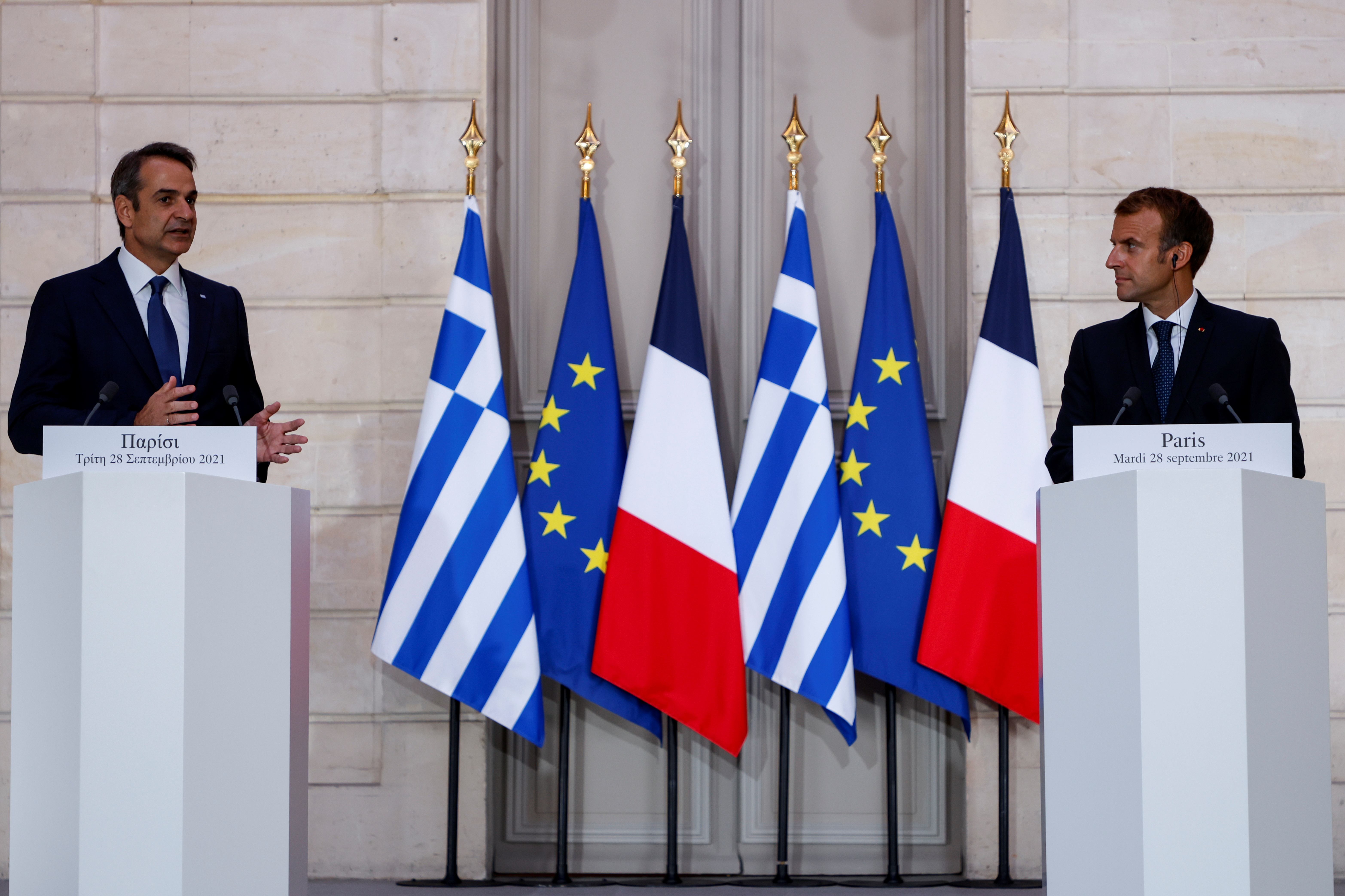 Greek Prime Minister Kyriakos Mitsotakis speaks as French President Emmanuel Macron listens on during a signing ceremony of a new defence deal at The Elysee Palace in Paris, France September 28, 2021. Ludovic Marin/Pool via REUTERS