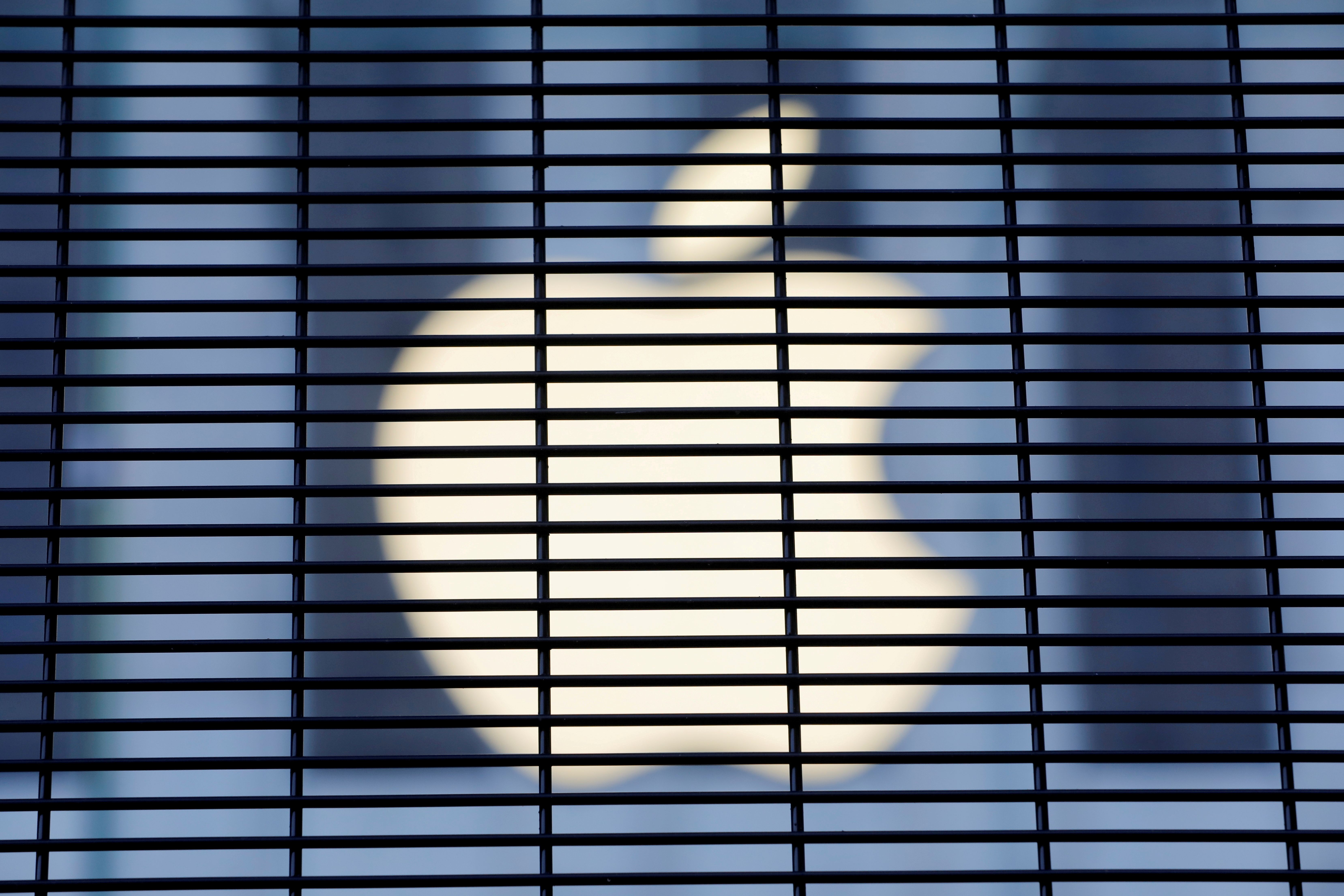 The Apple logo is seen through a security fence erected around the Apple Fifth Avenue store in Manhattan, New York City, U.S., November 5, 2020. REUTERS/Andrew Kelly
