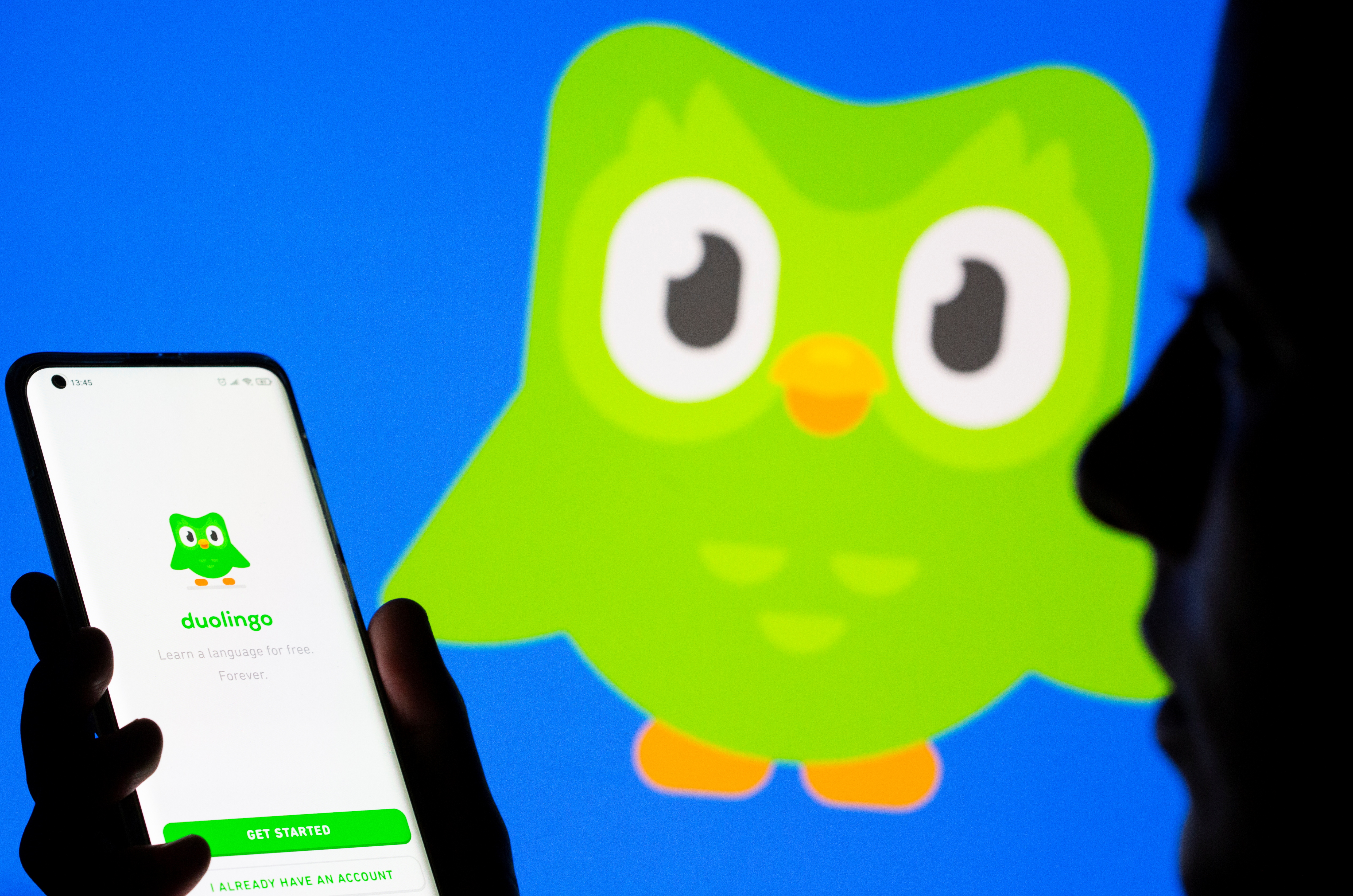 Woman with her smartphone poses in front of displayed Duolingo logo in this illustration taken, June 29, 2021. REUTERS/Dado Ruvic/Illustration