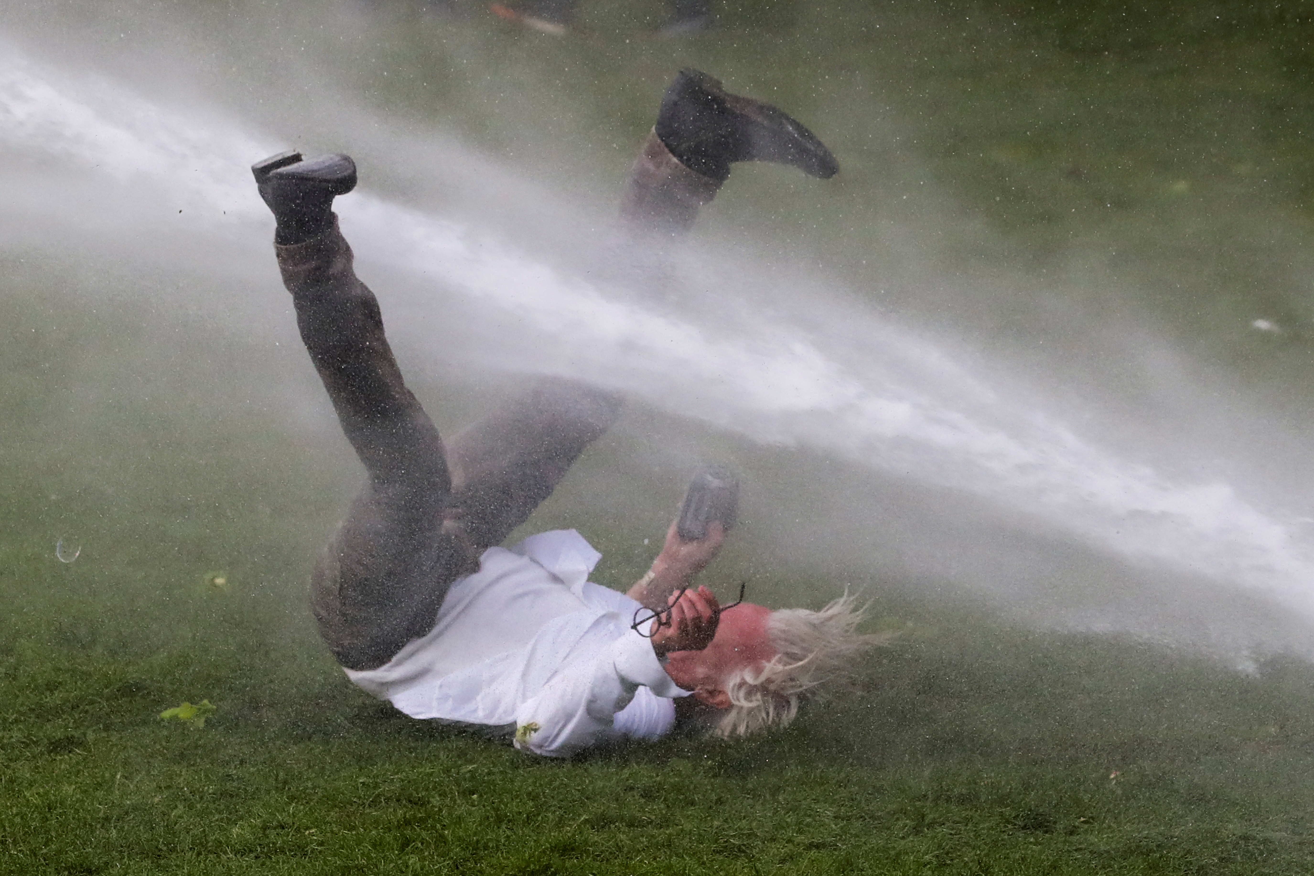 "A man is doused by a water cannon during clashes as people gather at the Bois de la Cambre/Ter Kamerenbos park for a party called ""La Boum 2"" in defiance of Belgium's coronavirus disease (COVID-19) social distancing measures and restrictions, in Brussels, Belgium May 1, 2021. REUTERS/Yves Herman"