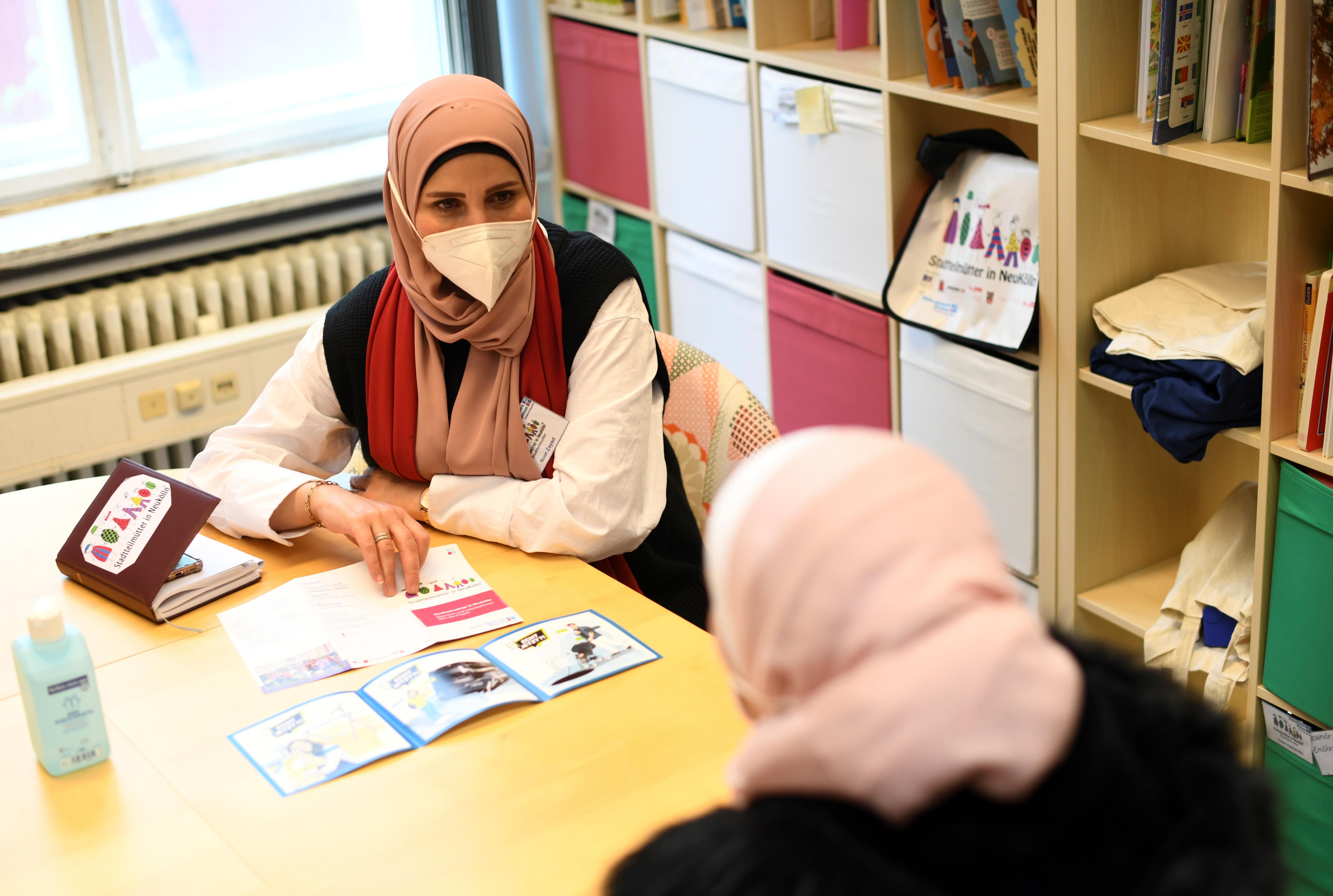 الأخصائية الاجتماعية نور زايد من مشروع Stadtteilmuetter لإدماج المهاجرين الذي تديره جمعية خيرية بروتستانتية دياكوني تتحدث إلى أم وجيه ، وهي أم سورية لطفلين ، في حي نويكولن في برلين ، 4 مايو 2021. تم التقاط الصورة في 4 مايو 2021. REUTERS / Annegret Hilse