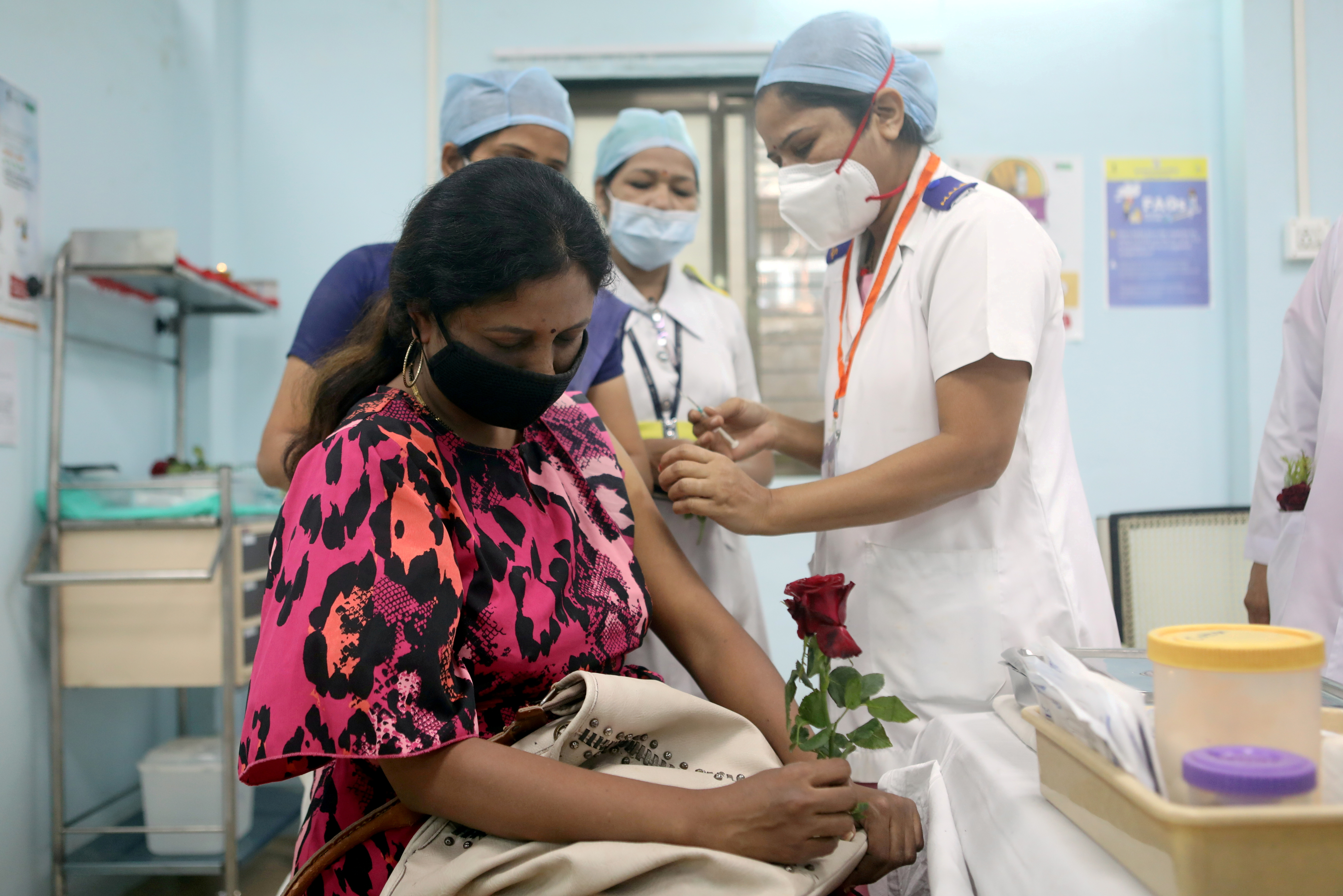 A healthcare worker holding a rose is vaccinated against COVID-19 at a medical centre in Mumbai, India, January 16, 2021. REUTERS/Francis Mascarenhas/File Photo
