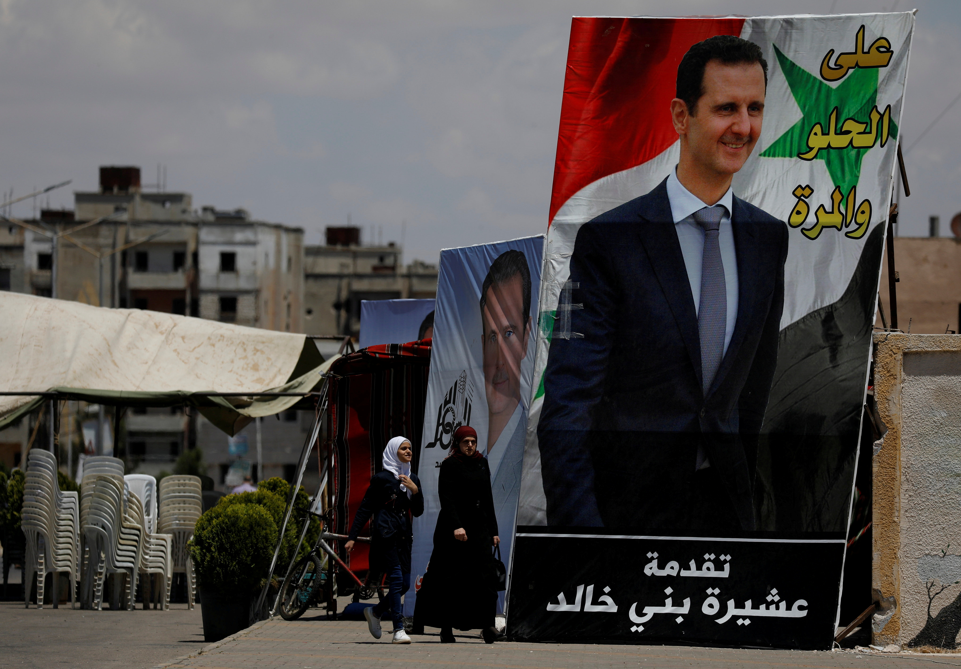 People walk past posters depciting Syria's President Bashar al-Assad, ahead of the May 26 presidential election, in the district of al-Waer in Homs, Syria May 23, 2021.  Picture taken May 23, 2021. REUTERS/Omar Sanadiki/File Photo