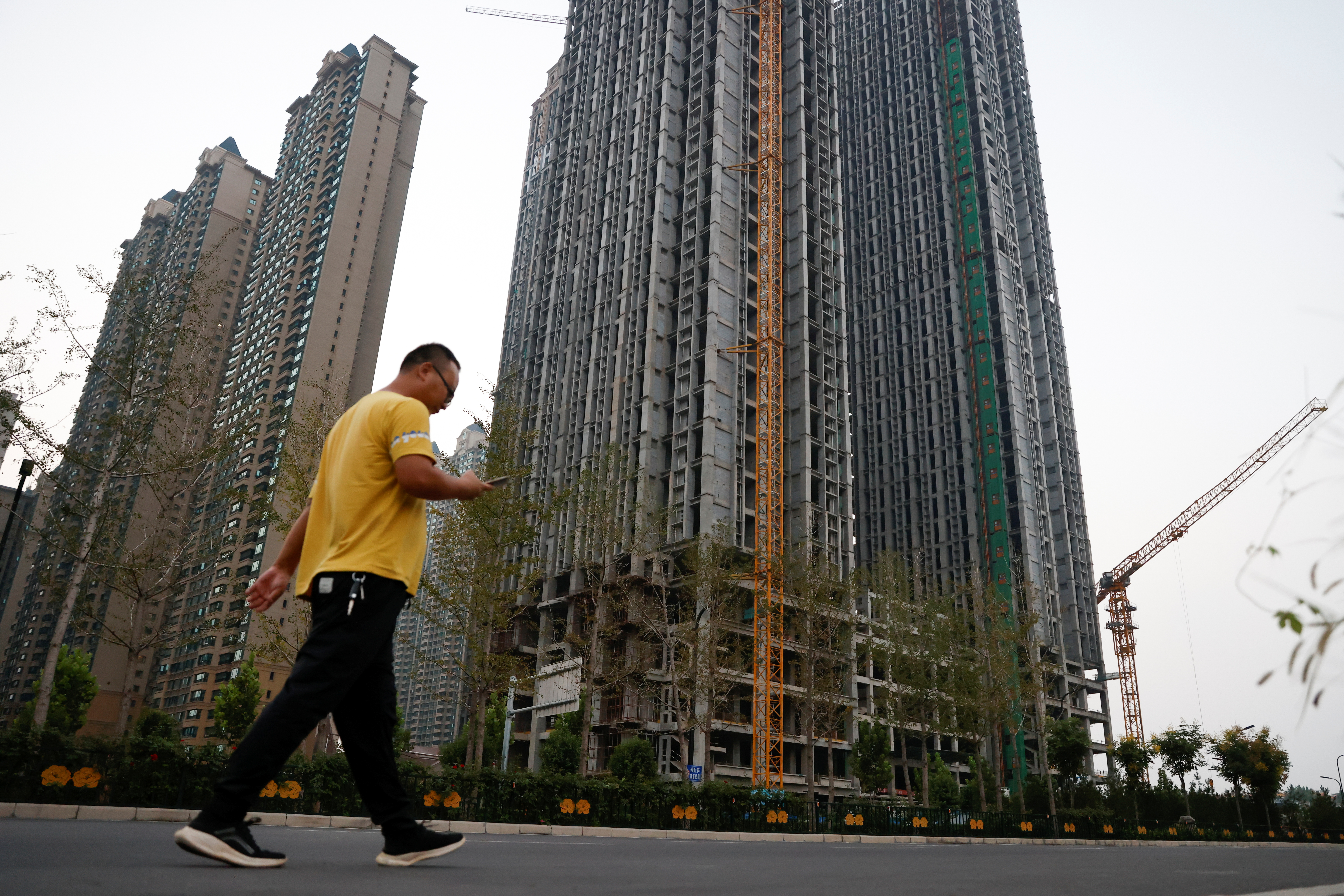 A man walks in front of unfinished residential buildings at the Evergrande Oasis, a housing complex developed by Evergrande Group, in Luoyang, China September 15, 2021. Picture taken September 15, 2021. REUTERS/Carlos Garcia Rawlins
