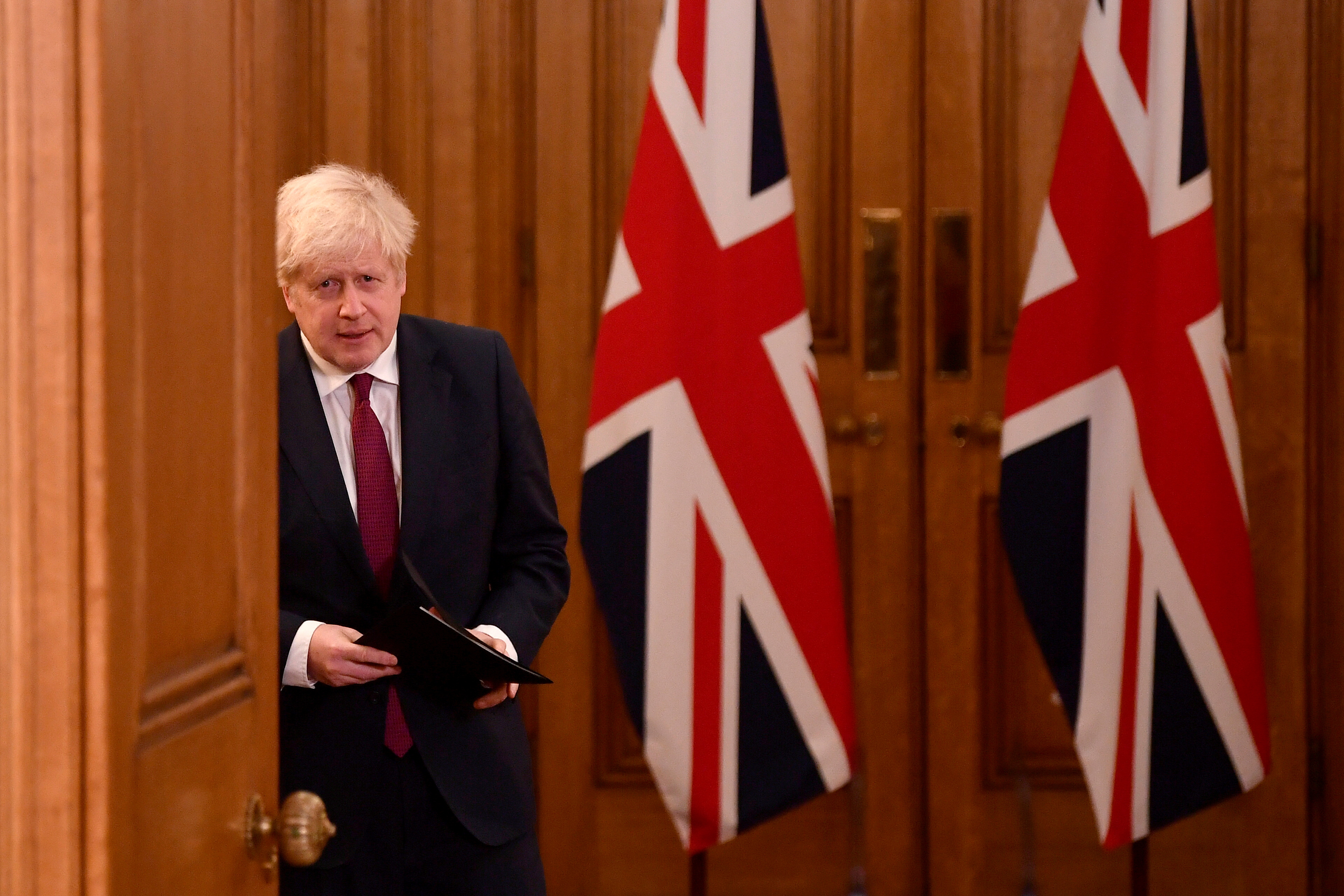 Britain's Prime Minister Boris Johnson arrives to attend a news conference in response to the ongoing situation with the coronavirus disease (COVID-19) pandemic, inside 10 Downing Street, London ,Britain, December 19, 2020. REUTERS/Toby Melville/Pool