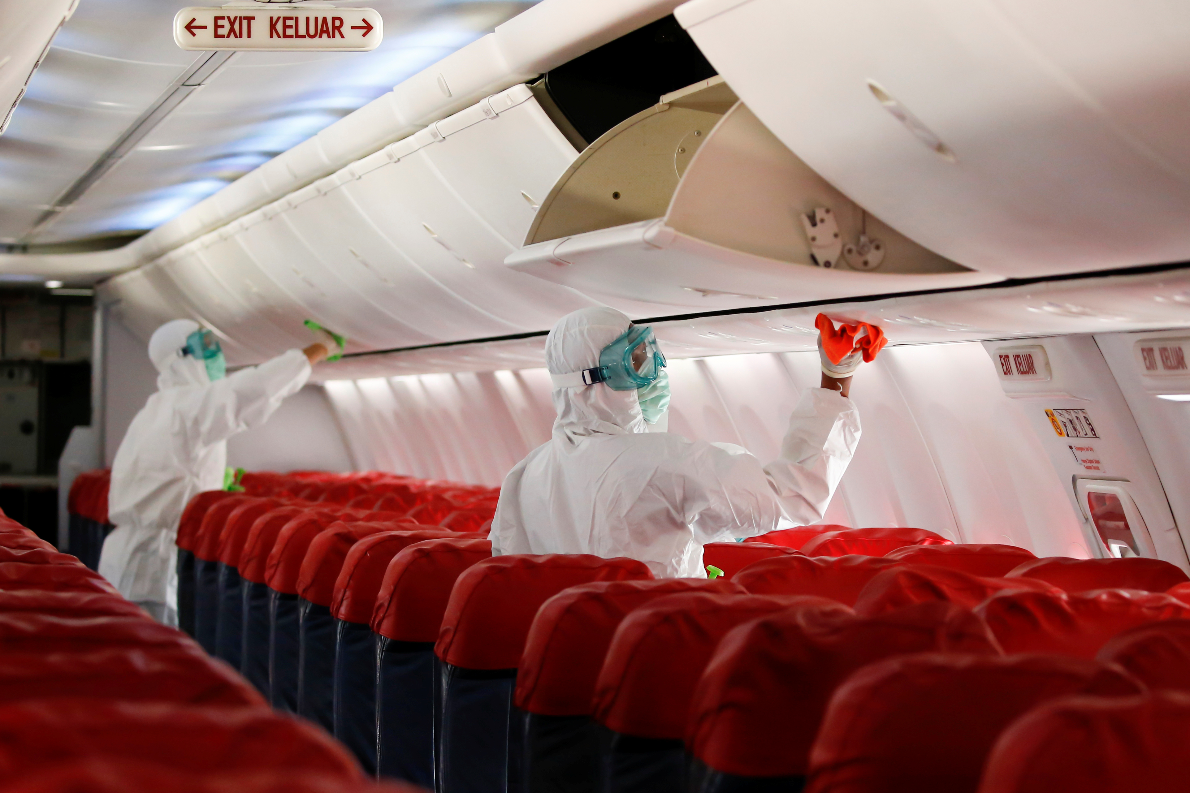 Cleaning workers, wearing protective suits, spray disinfectant inside the cabin of a Lion Air's Boeing 737-800, amid the spread of coronavirus disease (COVID-19), at Soekarno-Hatta International Airport near Jakarta, Indonesia, March 17, 2020. REUTERS/Willy Kurniawan/Files