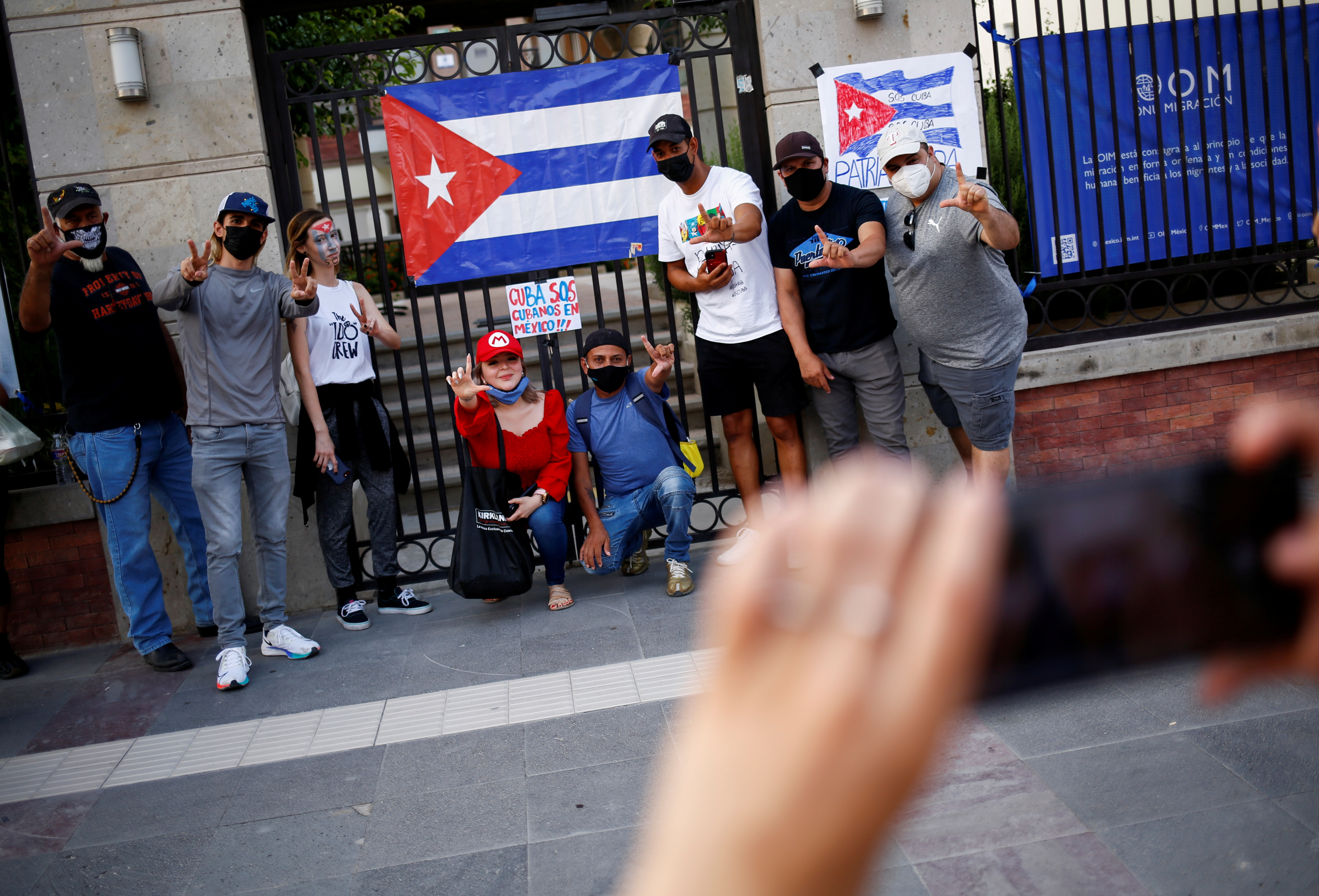 Cubans gesture during a protest against the Cuban government in front of the offices of the International Organization for Migration (IOM) in Ciudad Juarez, Mexico July 12, 2021. REUTERS/Jose Luis Gonzalez/File Photo