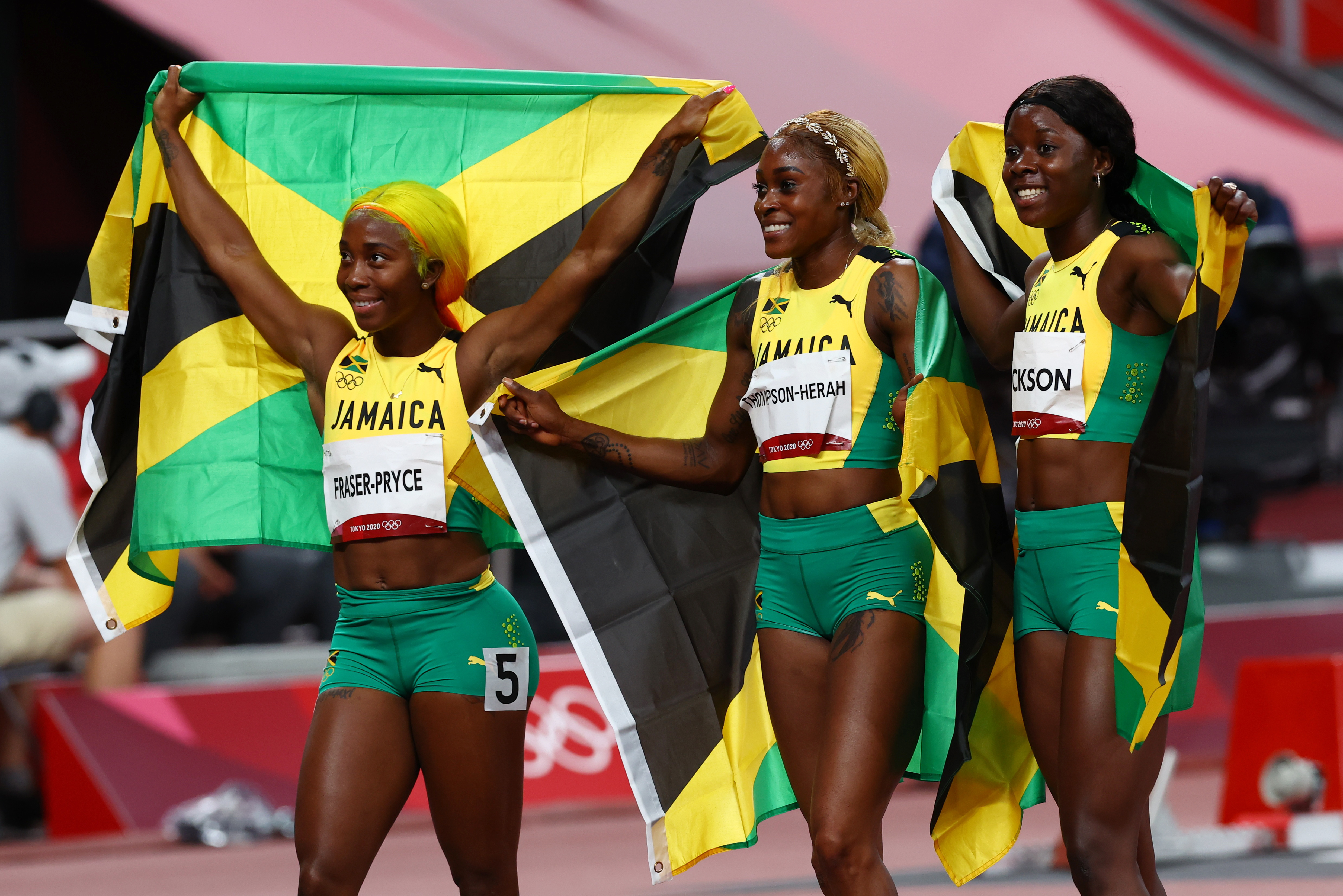 Tokyo 2020 Olympics - Athletics - Women's 100m - Final - OLS - Olympic Stadium, Tokyo, Japan - July 31, 2021. Elaine Thompson-Herah of Jamaica celebrates winning the gold medal next to Shelly-Ann Fraser-Pryce of Jamaica who won the silver medal and Shericka Jackson of Jamaica who won the bronze medal REUTERS/Kai Pfaffenbach