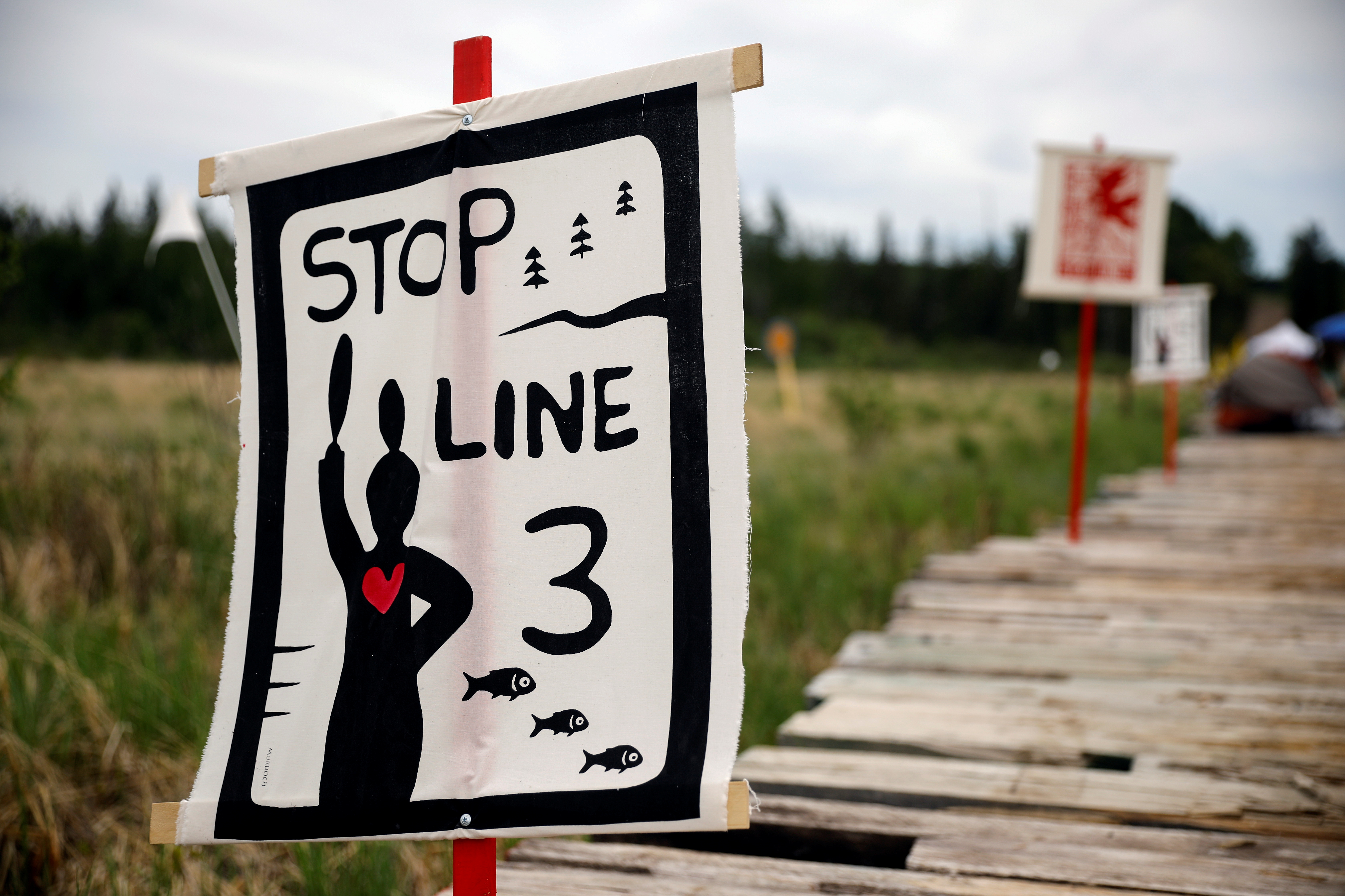 Protest signage on display at a camp established by indigenous leaders and water protectors at the Mississippi headwaters, one body of water the Line 3 pipeline will cross following a series of demonstrations in protest of the Line 3 pipeline, built by Enbridge Energy, in Solway, Minnesota, U.S., June 8, 2021. Picture taken June 8, 2021.  REUTERS/Nicholas Pfosi