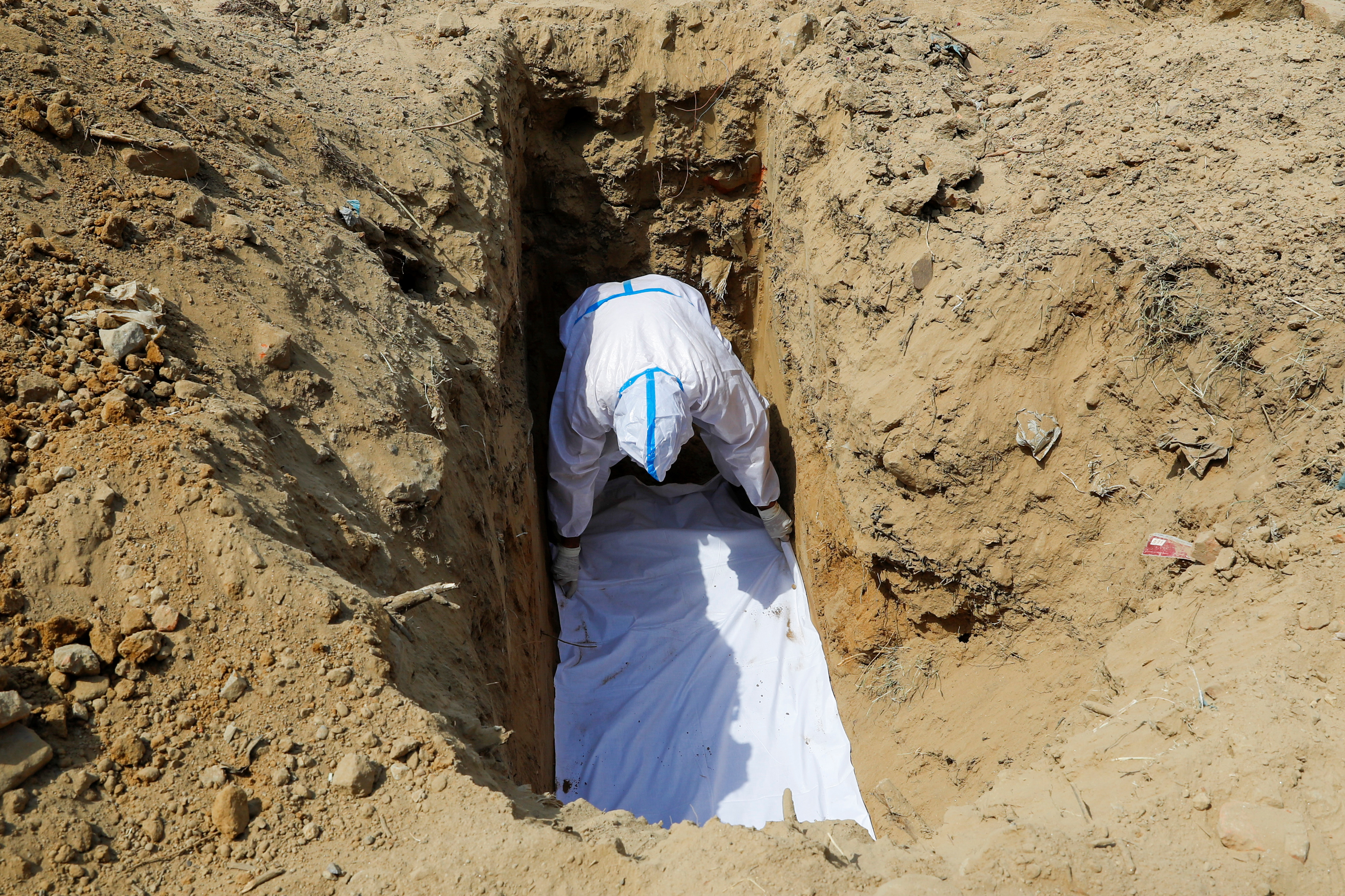 A family member wearing personal protective equipment (PPE) prepares a grave for a man who died from the coronavirus disease (COVID-19), during his funeral at a graveyard in New Delhi, India, April 23, 2021. REUTERS/Adnan Abidi