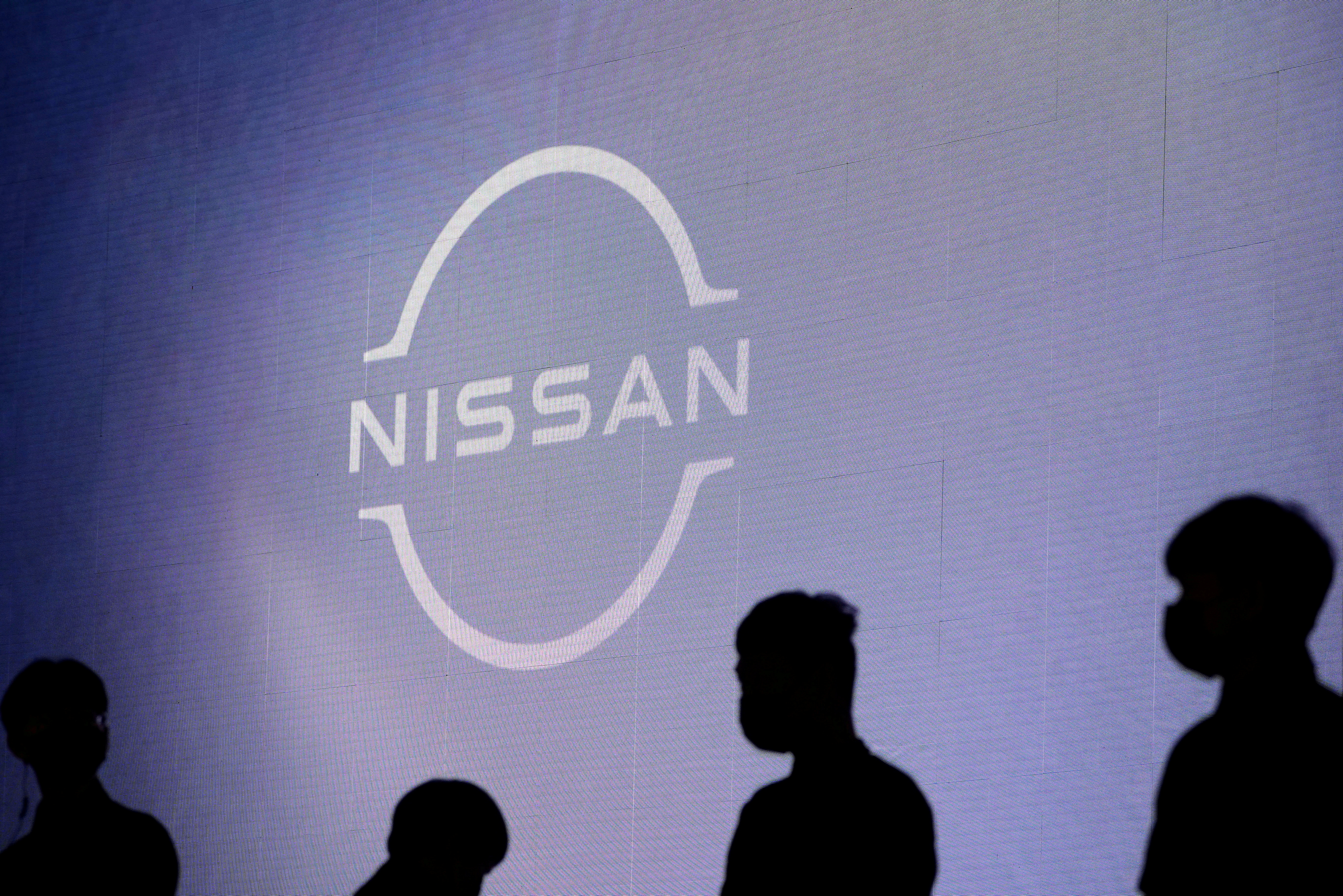 People stand near the Nissan logo during a media day for the Auto Shanghai show in Shanghai, China, April 20, 2021. REUTERS/Aly Song