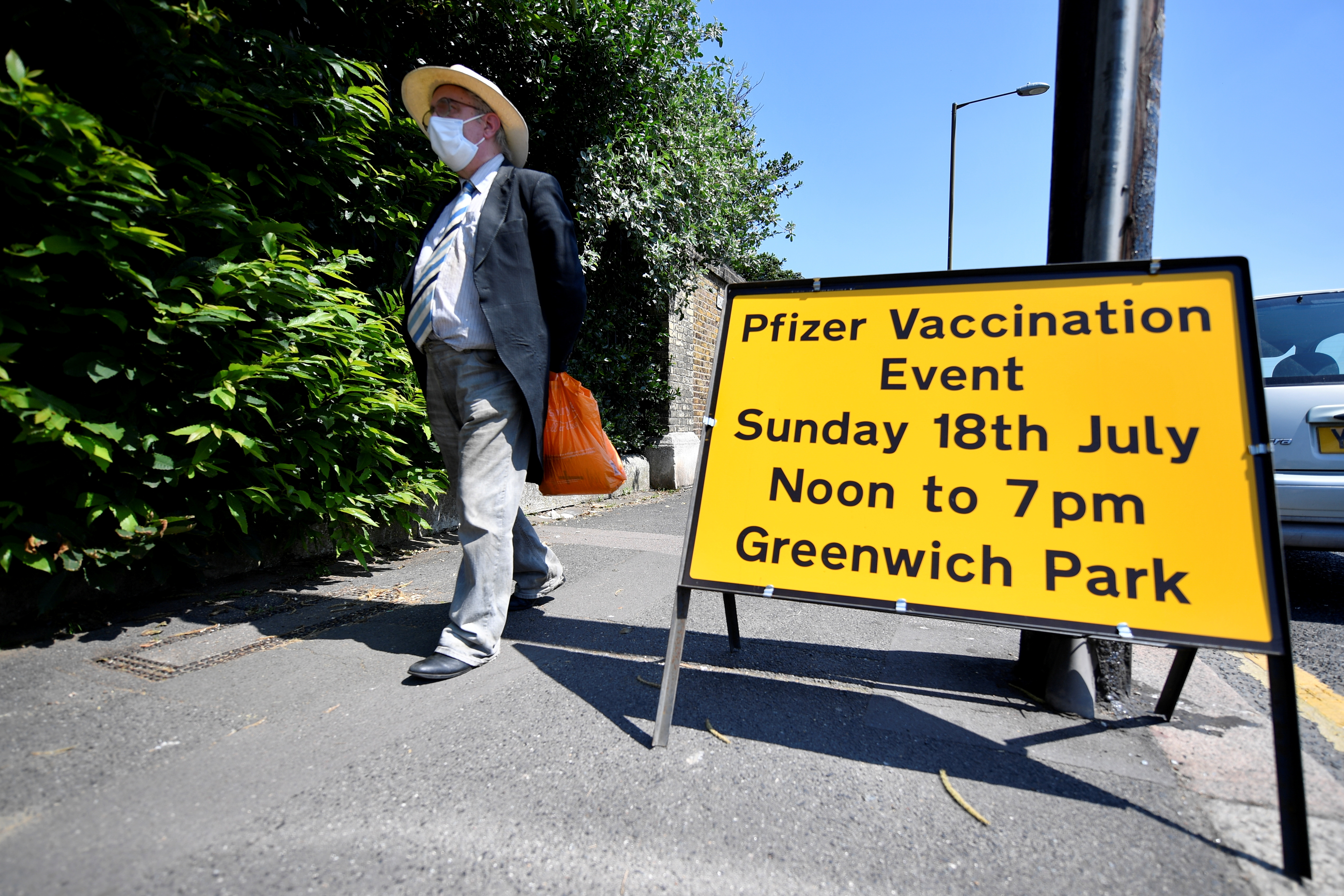 A person walks past a sign informing about a vaccination centre in Greenwich park, amid the coronavirus disease (COVID-19) outbreak, in London, Britain, July 18, 2021. REUTERS/Beresford Hodge