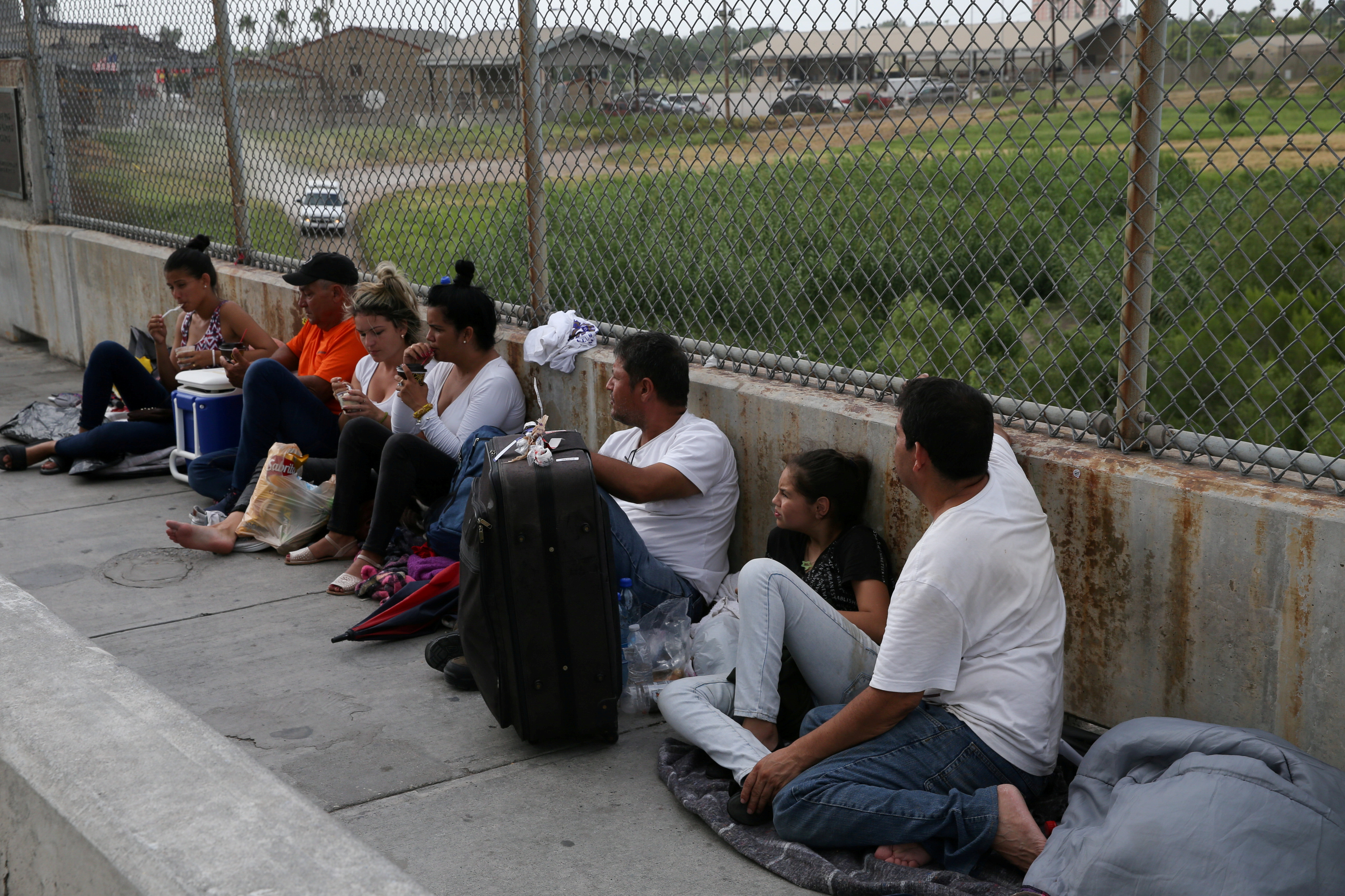 Asylum seekers wait on the Mexican side of the Brownsville-Matamoros International Bridge after being denied entry by U.S. Customs and Border Protection officers near Brownsville, Texas, U.S., July 25, 2018.  REUTERS/Loren Elliott/File Photo