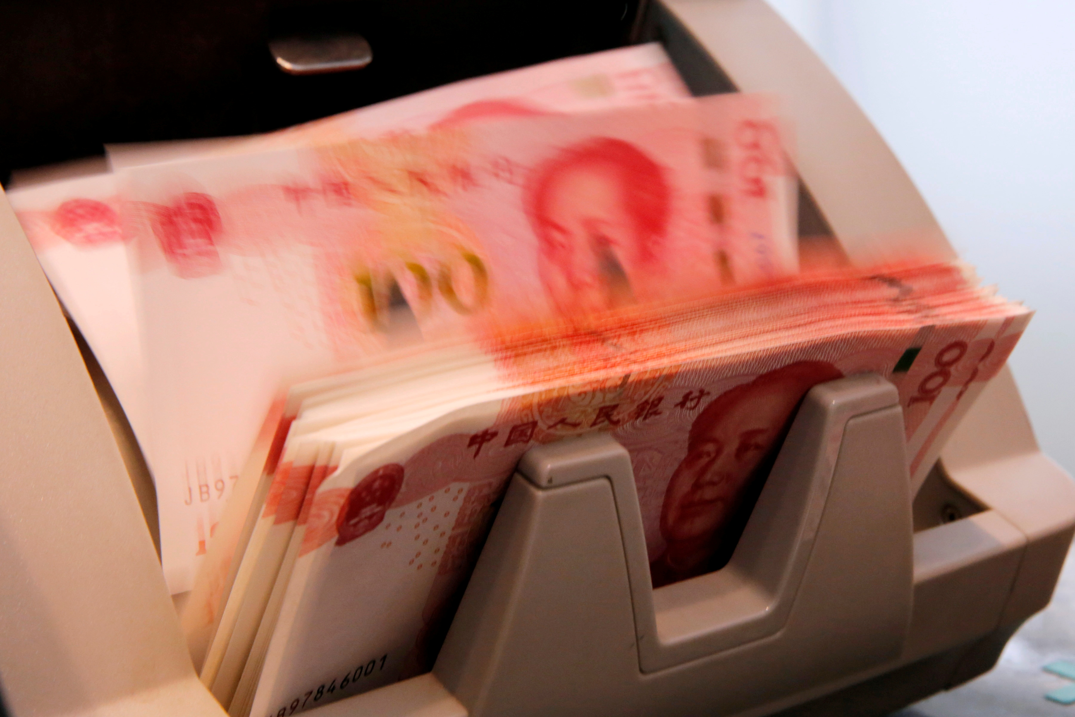 Chinese 100 yuan banknotes are seen in a counting machine while a clerk counts them at a branch of a commercial bank in Beijing, China, March 30, 2016. REUTERS/Kim Kyung-Hoon/File Photo