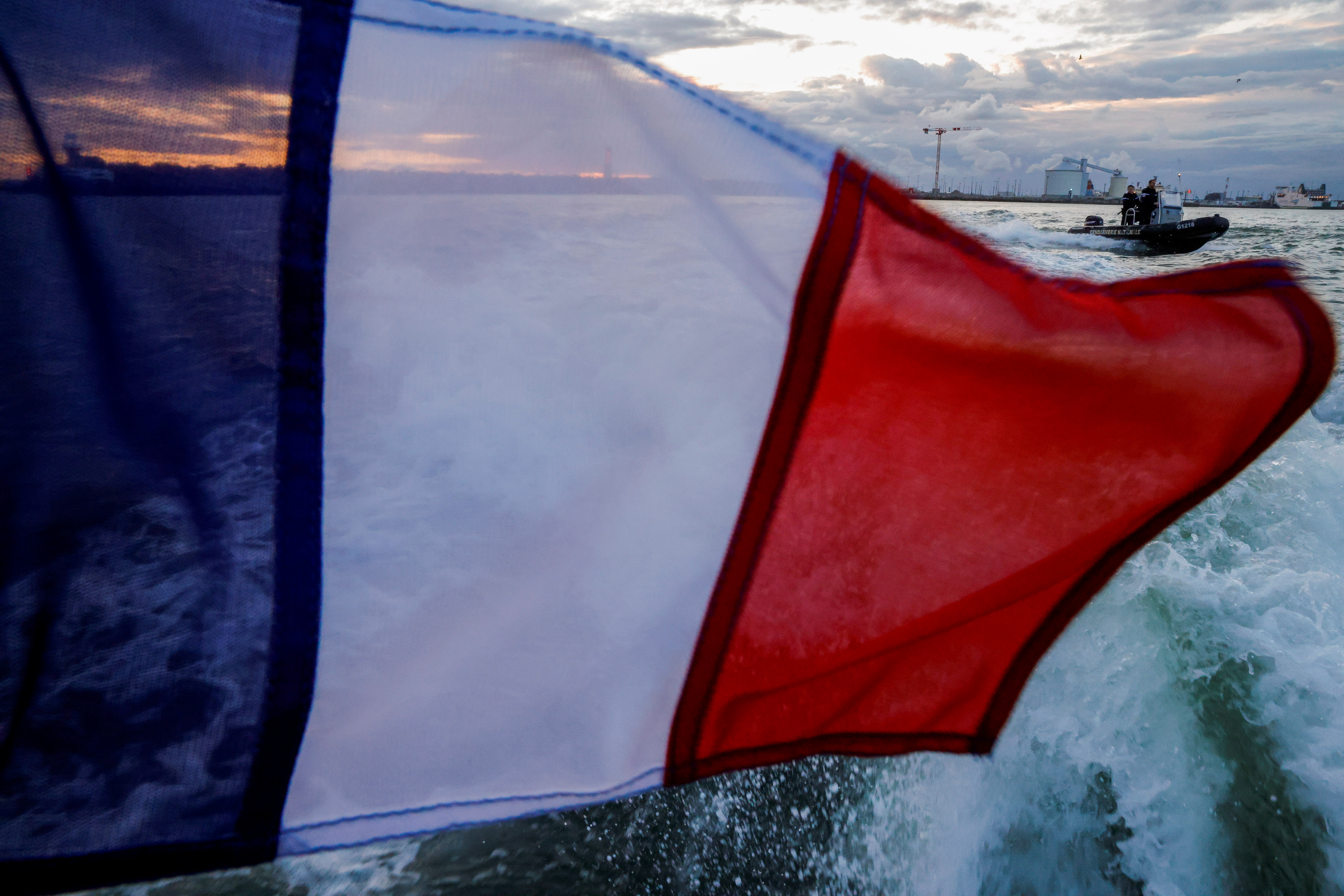 The flag of France is seen as French Gendarmerie officers patrol with a dinghy along the French coast near Calais, France August 2, 2021. REUTERS/Pascal Rossignol