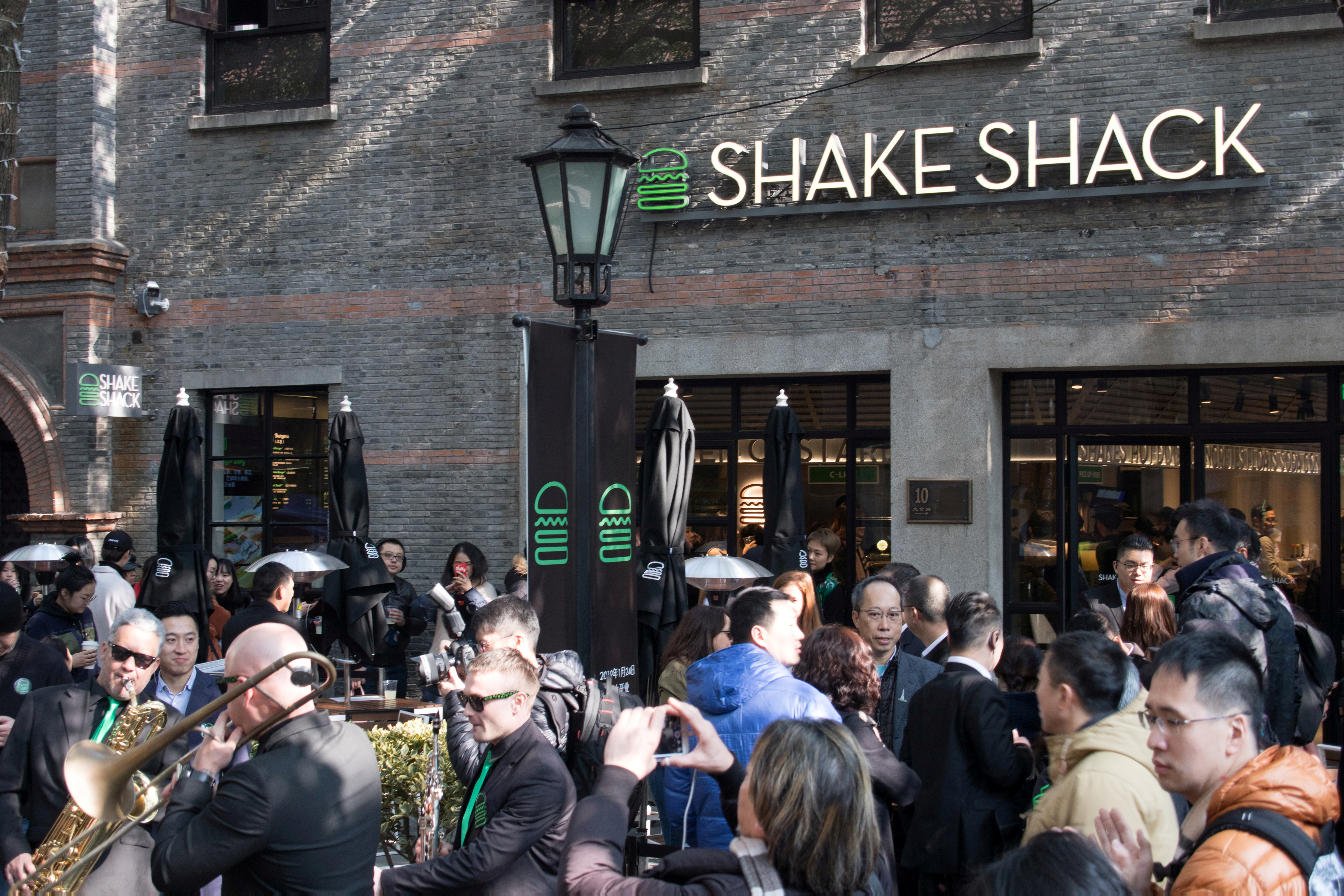 People gather in front of a restaurant of U.S. burger chain Shake Shack on its opening in Shanghai, China, January 24, 2019. REUTERS/Stringer