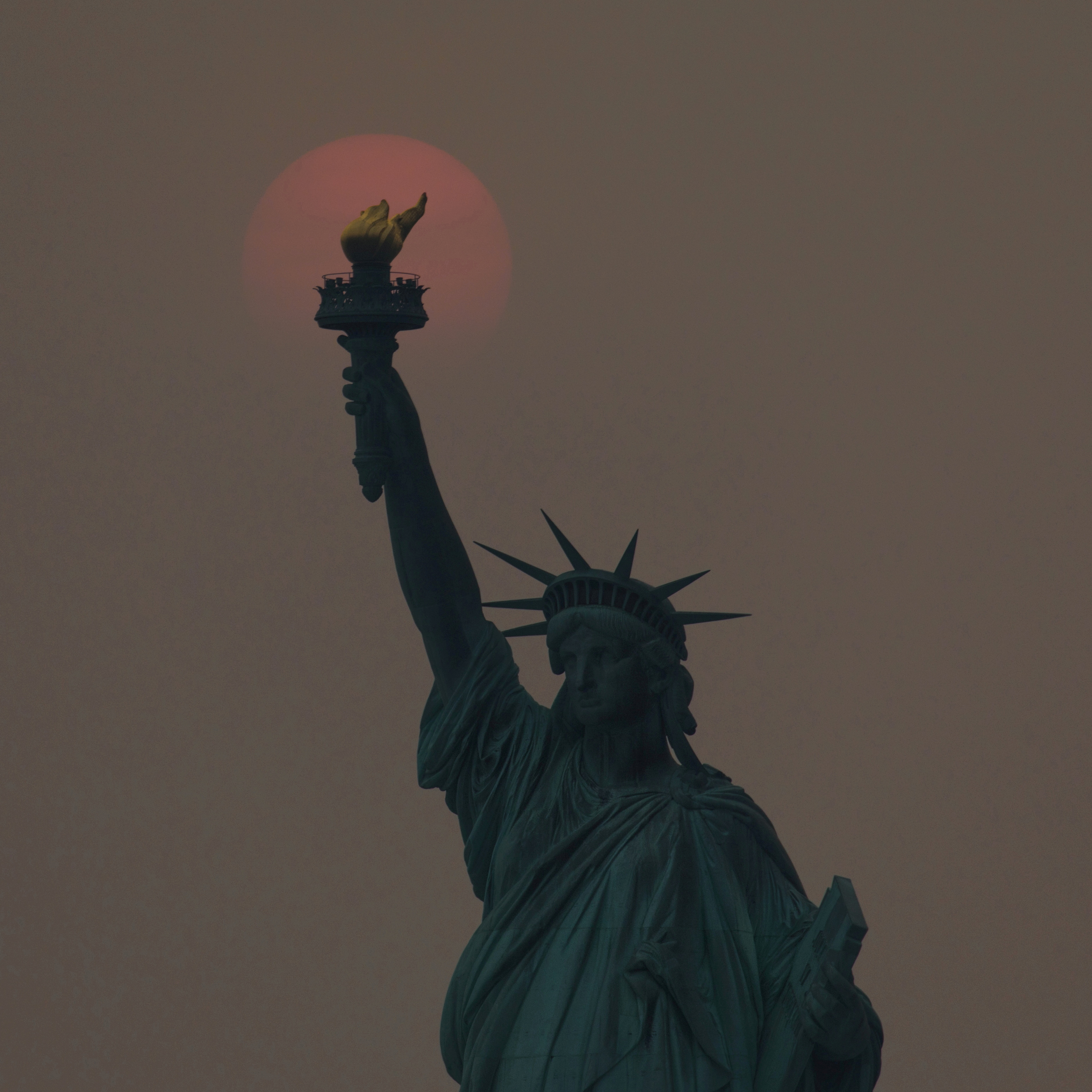 The sun, appearing orange due to smoke haze from forest fires, sets behind the Statue of Liberty in New York City, New York, U.S., July 20, 2021. Picture taken July 20, 2021. REUTERS/Bjoern Kils/New York Media Boat