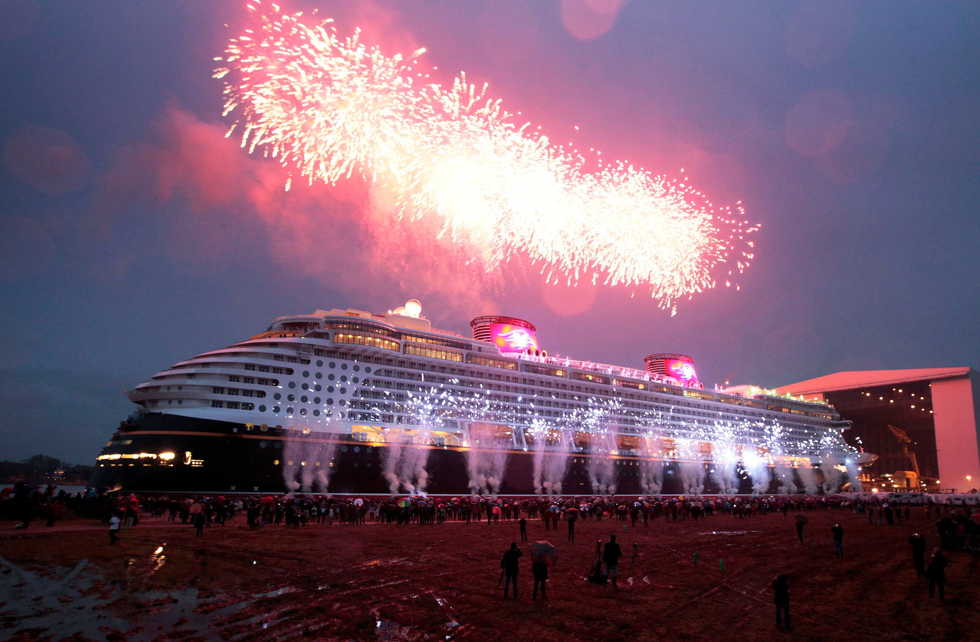 People watch the 'float out' of  the newly built cruise ship