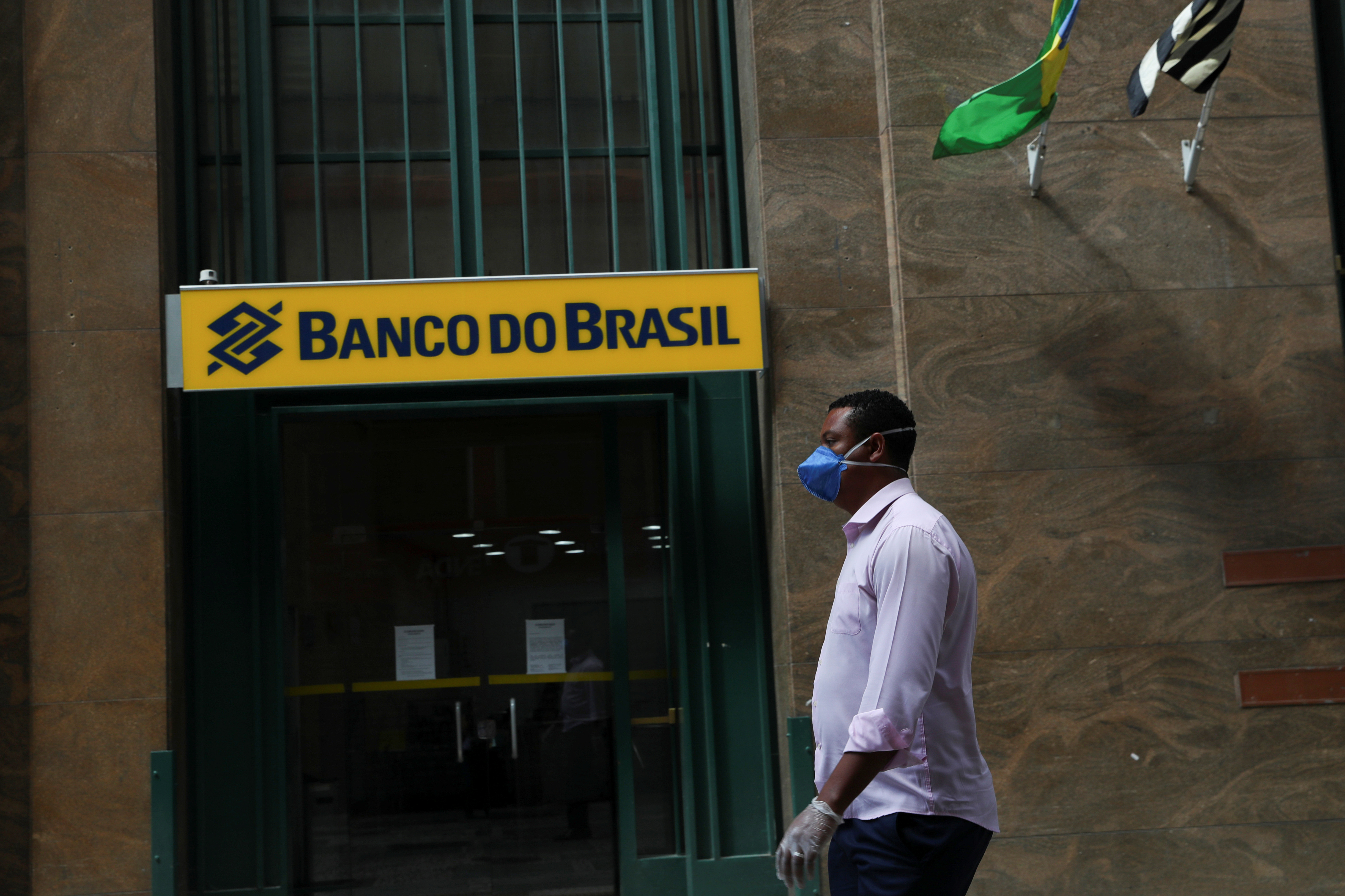 A man wearing a protective face mask and gloves walks in front of Banco do Brasil (Bank of Brazil) during the coronavirus disease (COVID-19) outbreak in Sao Paulo, Brazil, March 24, 2020. REUTERS/Amanda Perobelli/File Photo