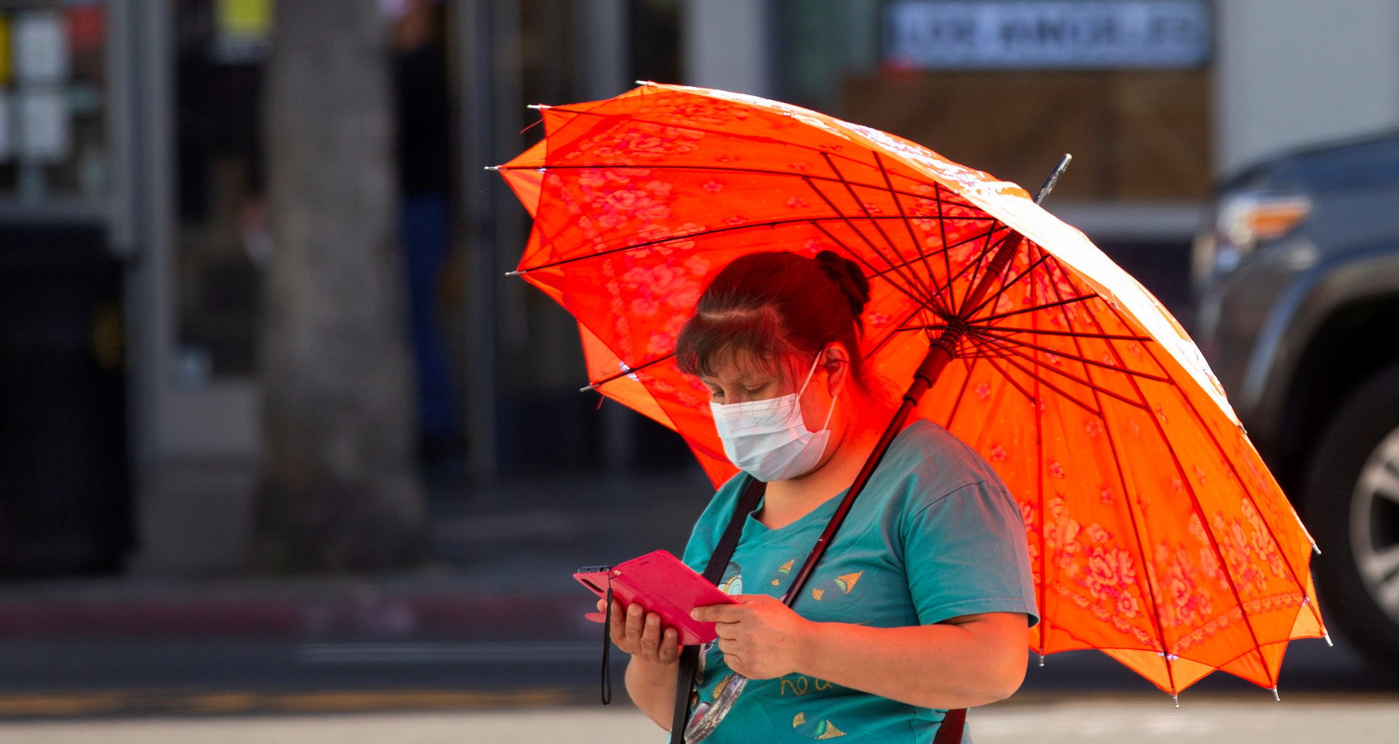 A person wearing a protective face mask uses her mobile phone during the outbreak of the coronavirus disease (COVID-19), in Los Angeles, California, U.S., March 31, 2021.  REUTERS/Mario Anzuoni/File Photo