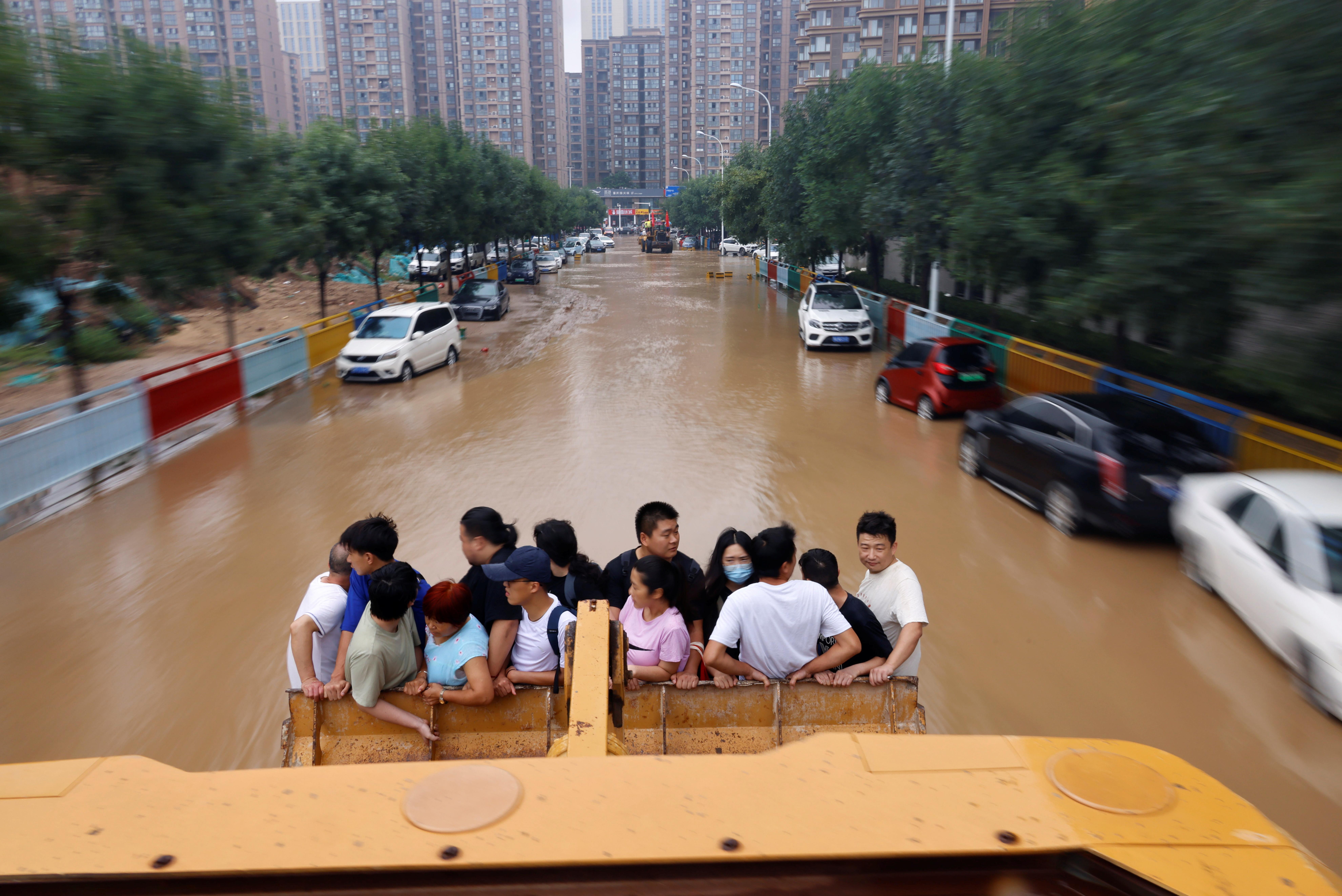 Mọi người đi xe tải phía trước khi họ băng qua một con đường ngập lụt sau trận mưa lớn ở Trịnh Châu, tỉnh Hà Nam, Trung Quốc ngày 23 tháng 7 năm 2021. REUTERS / Aly Song