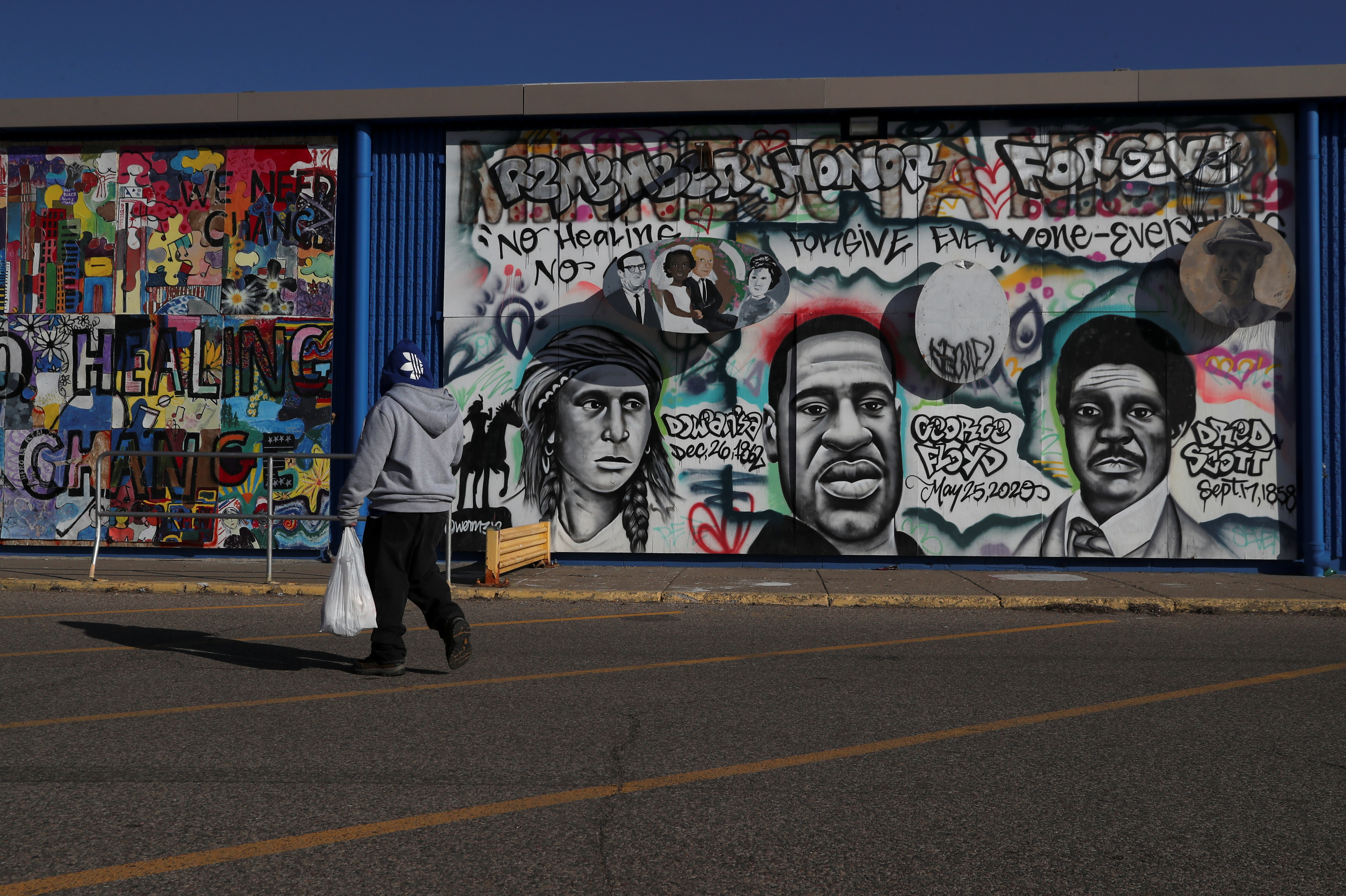 A pedestrian walks past community murals painted on the side of what was the Lake Street Kmart, which was destroyed in the wake of George Floyd's death, as jury selection continues in the trial of former Minneapolis police officer Derek Chauvin, on murder charges in the death of George Floyd in Minneapolis, Minnesota, U.S., March 12, 2021. Picture taken March 12, 2021. REUTERS/Leah Millis