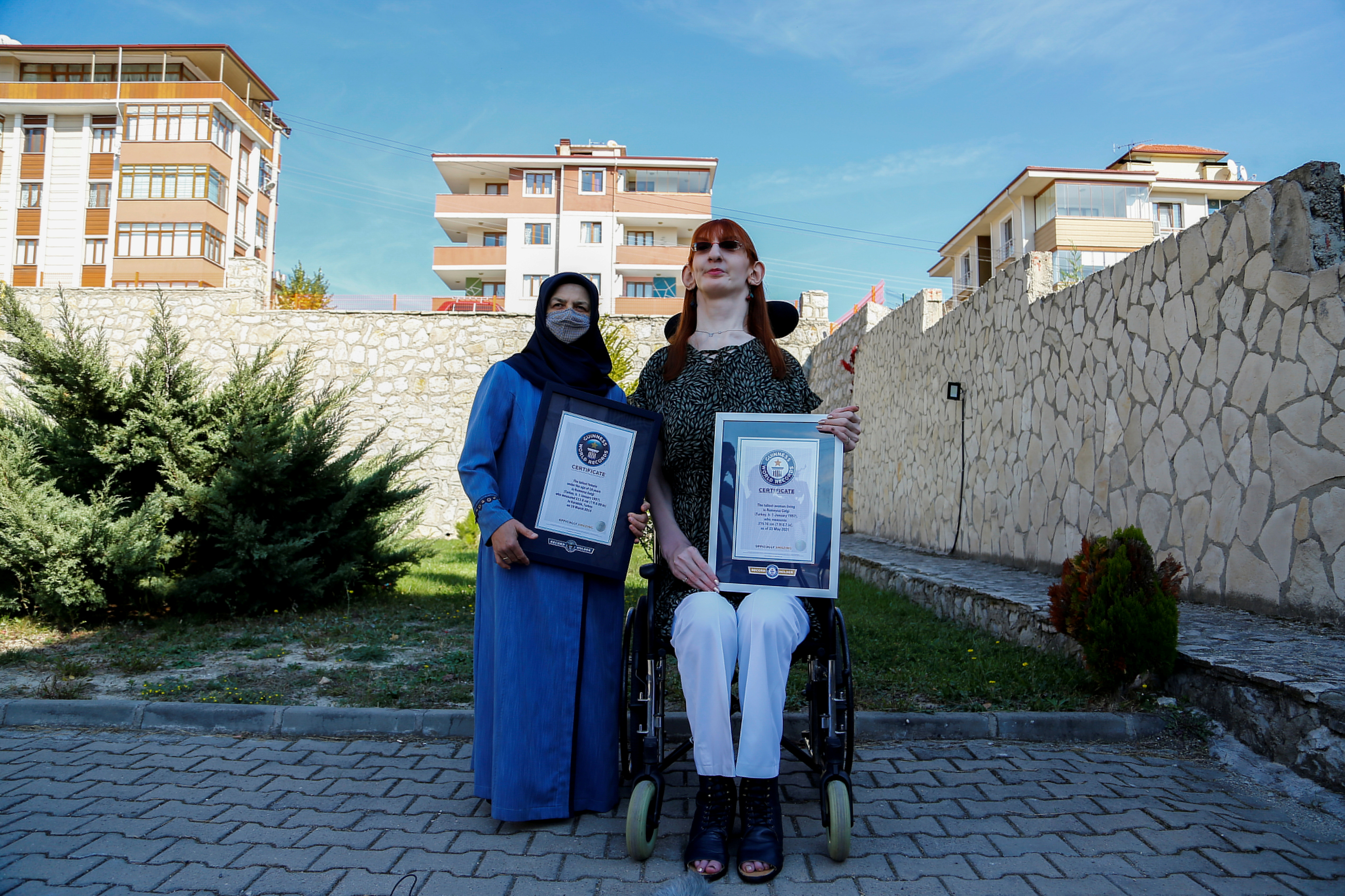 World's tallest woman Rumeysa Gelgi, accompanied by her mother Safiye Gelgi, holds the Guinness World Record certificates during a news conference outside their home in Safranbolu, Karabuk province, Turkey, October 14, 2021. REUTERS/Cagla Gurdogan