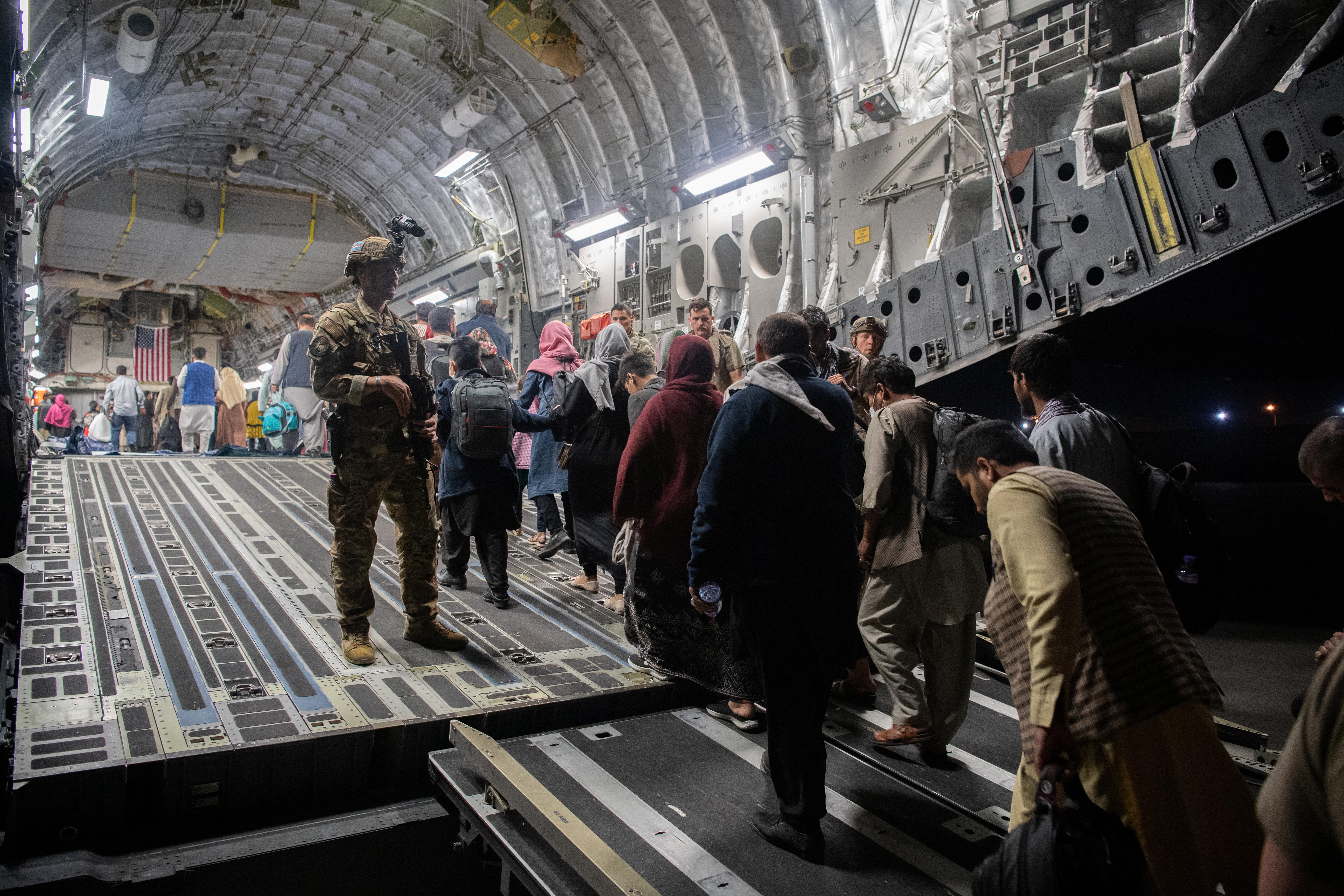 Afghans board a U.S. Air Force C-17 Globemaster III transport plane during an evacuation at Hamid Karzai International Airport, Afghanistan, August 22, 2021. U.S. Air Force/Handout via REUTERS