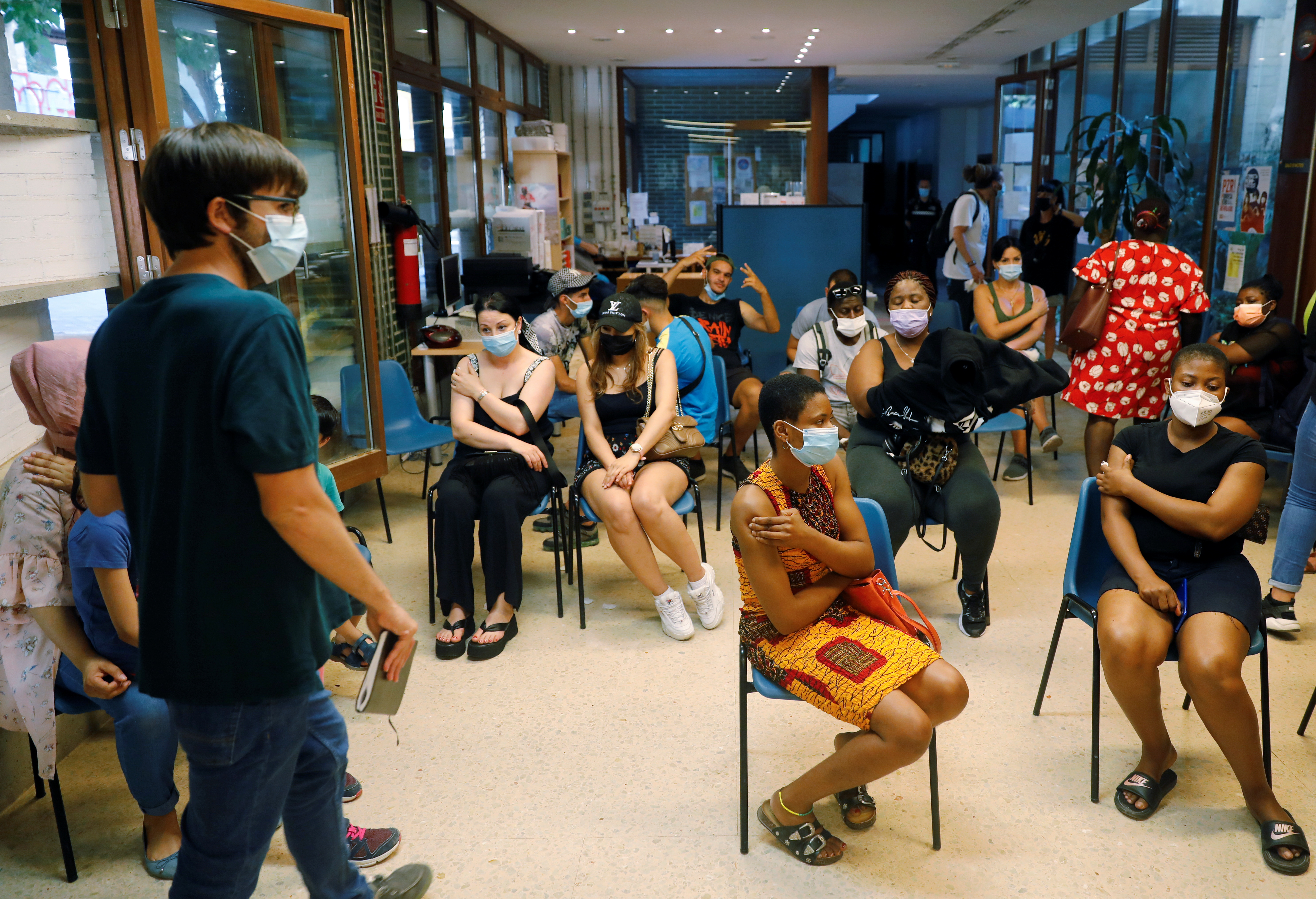 People wait after receiving their Johnson & Johnson's coronavirus disease (COVID-19) vaccine during a vaccination rollout for homeless at a vaccination centre in Valencia, Spain, July 15, 2021. REUTERS/Eva Manez
