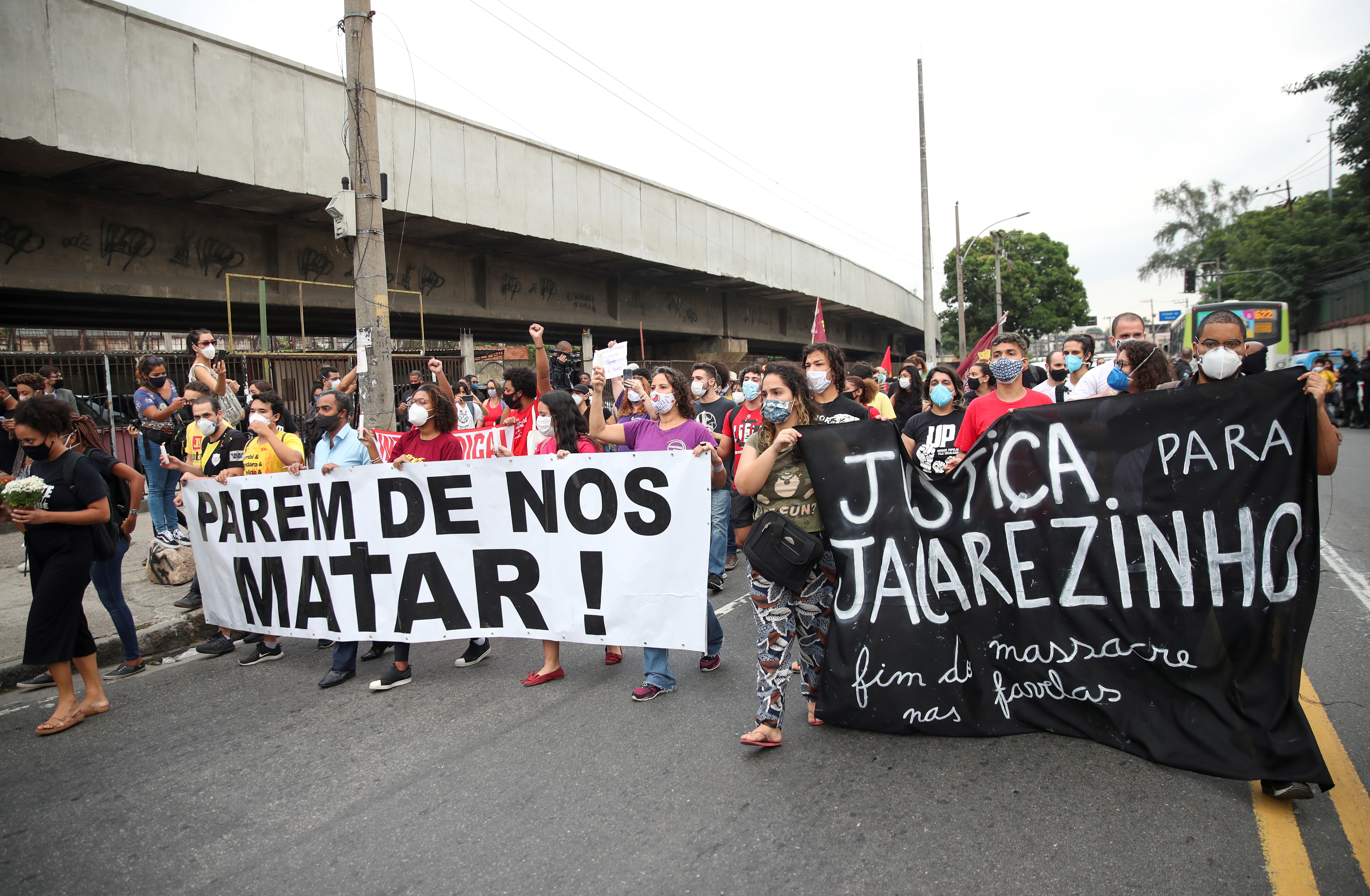 People attend a protest against police violence outside Jacarezinho slum after a police operation which resulted in 25 deaths in Rio de Janeiro, Brazil, May 7, 2021. Banners read: