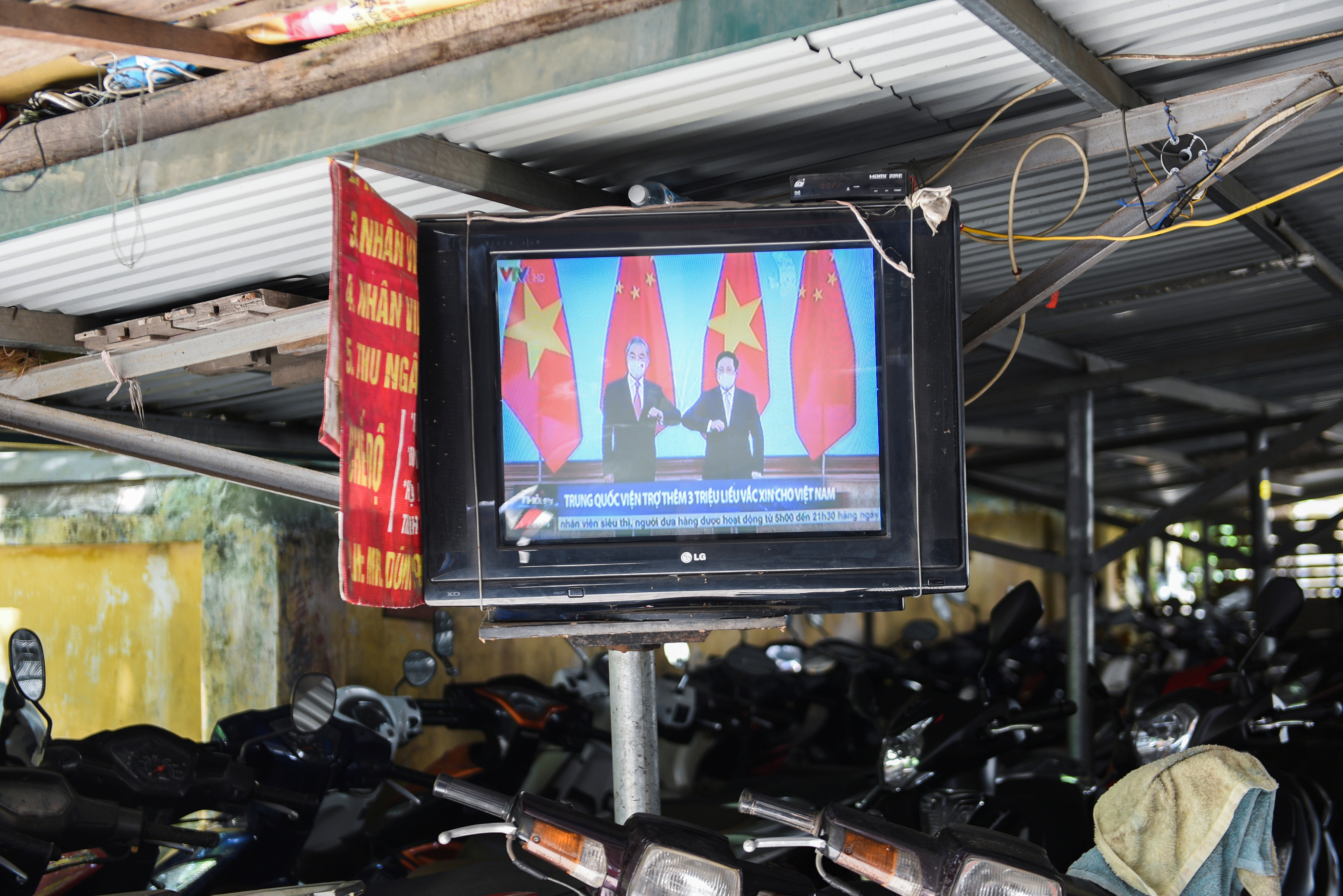 A television displays news about Chinese foreign minister Wang Yi's visit to Vietnam, at a street in Hanoi, Vietnam, September 11, 2021. REUTERS/Stringer